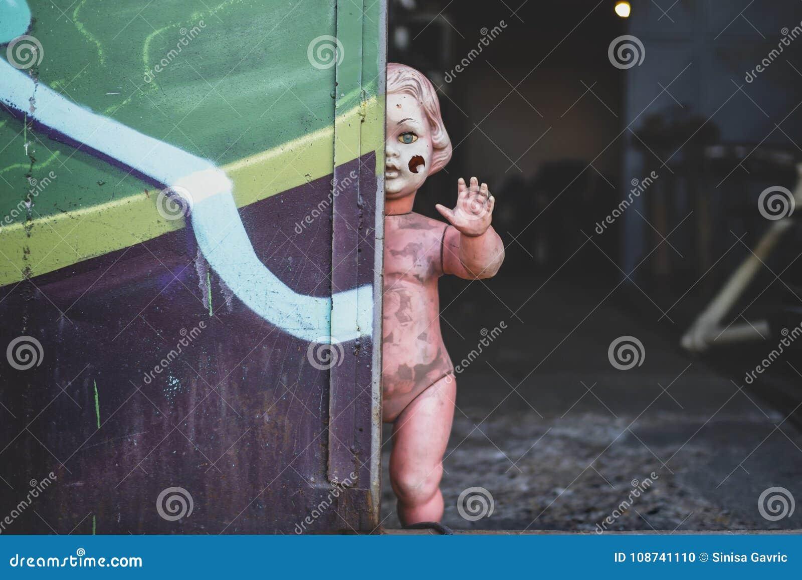 Smutsigt plast- naket behandla som ett barn - dockaanseendet vid dörren på metallen shoppar att se kusligt och jagat väva