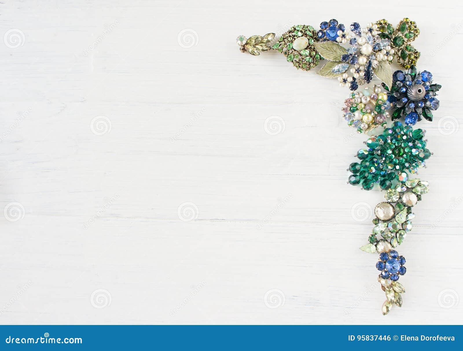 Smycken för kvinna` s Tappningsmyckenbakgrund Härlig ljus bergkristallbrosch, halsband och örhängen på vitt trä Lekmanna- lägenhe