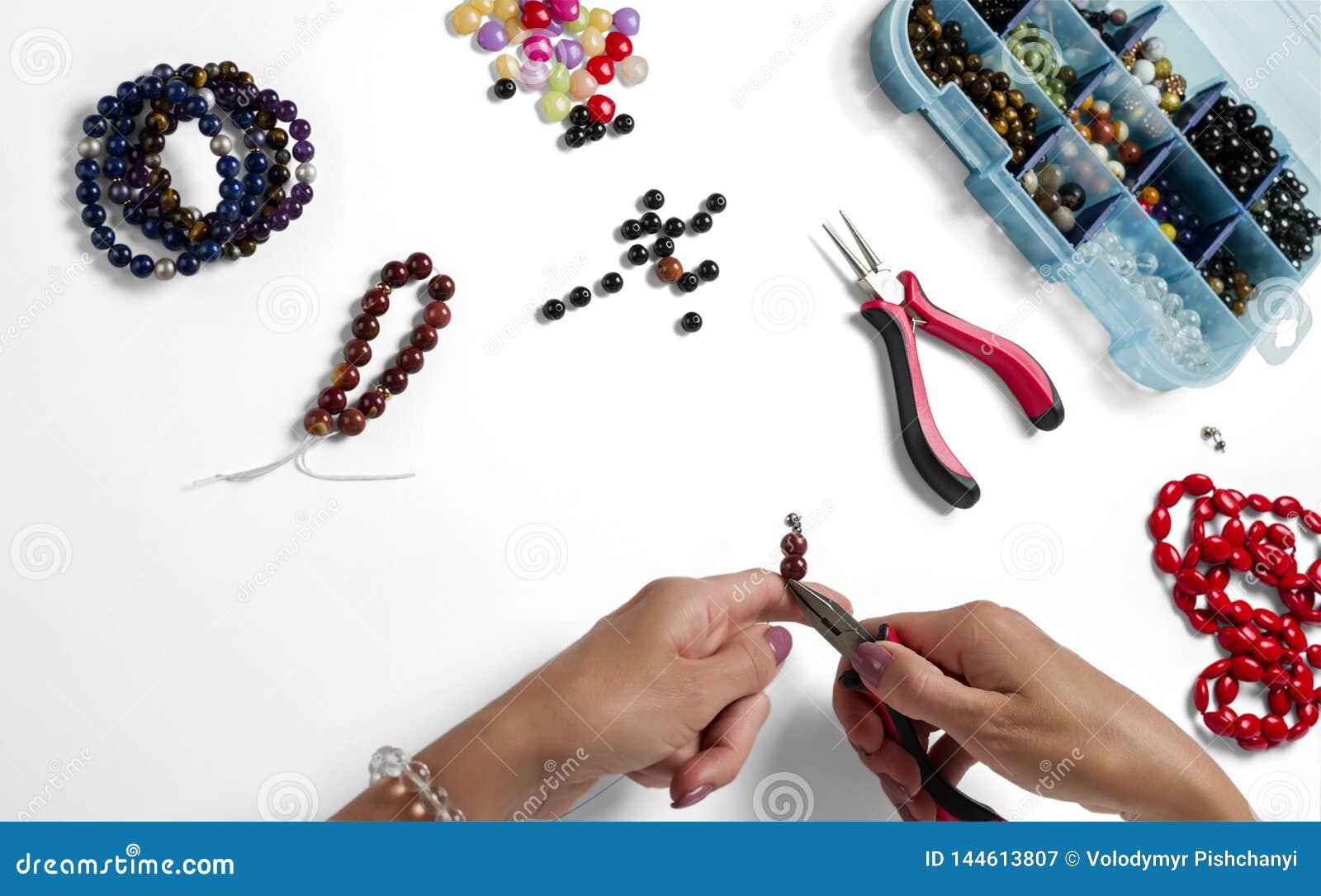 Smyckendanande Produktionarmband och halsband fr?n m?ng--f?rgade p?rlor p? en vit