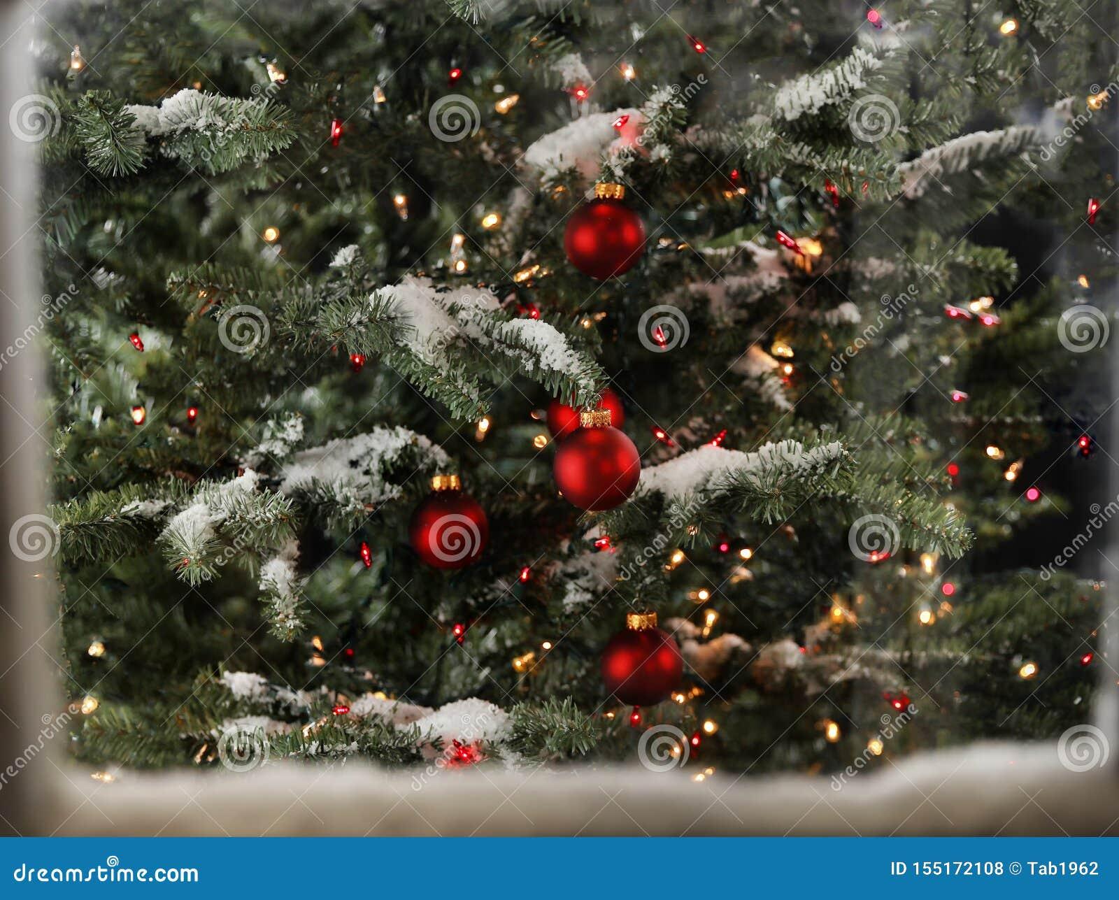 Snö täckte fönstret med julgranen och glödande ljus