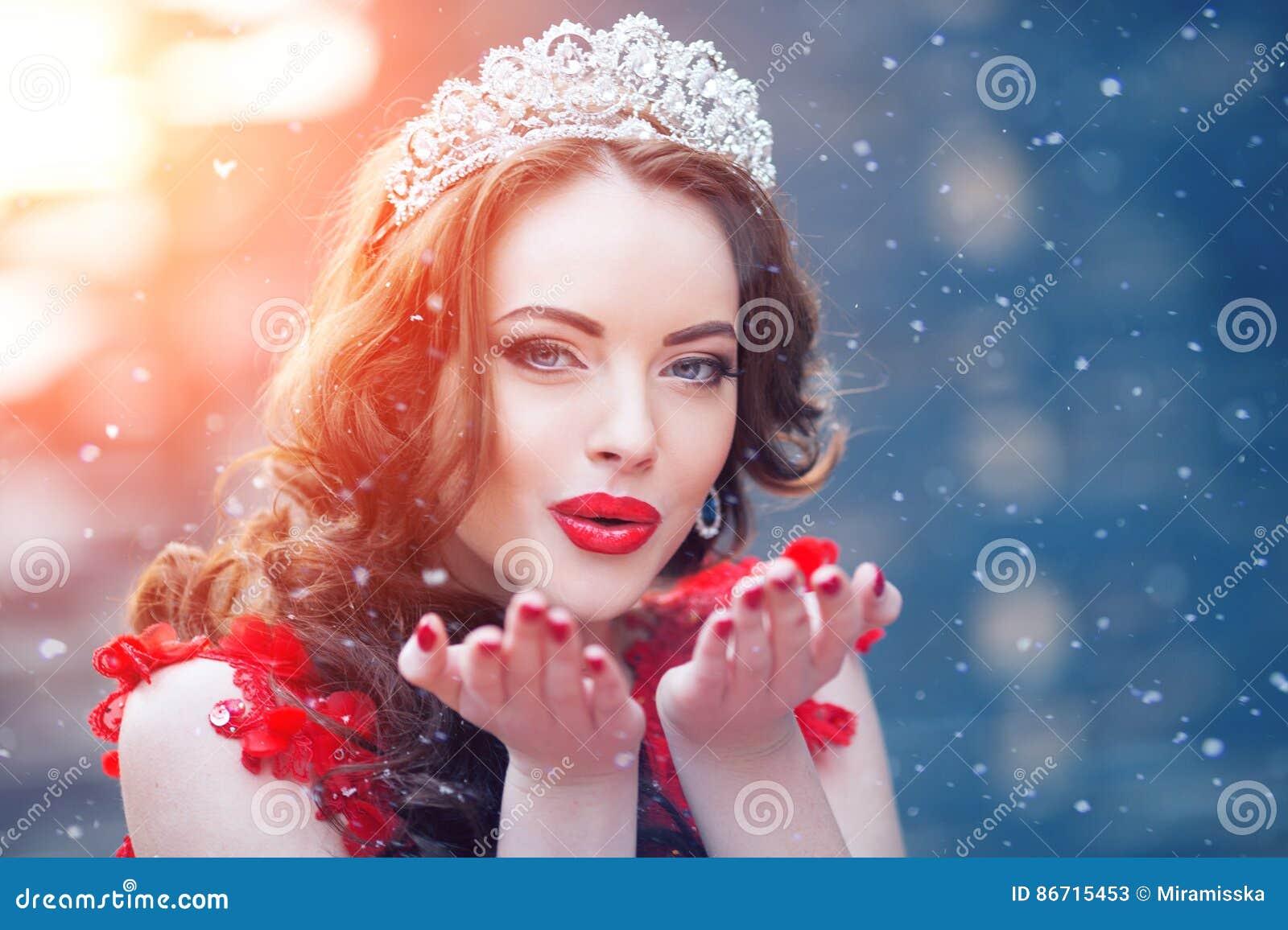 Snödrottning i rött Övervintra kvinnan i krona i en röd klänning och rött