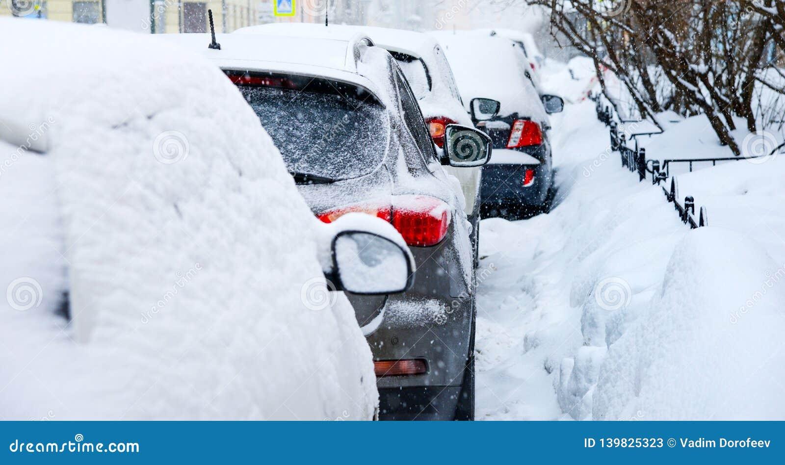 Snöfall i staden Ett antal bilar som täckas i snö