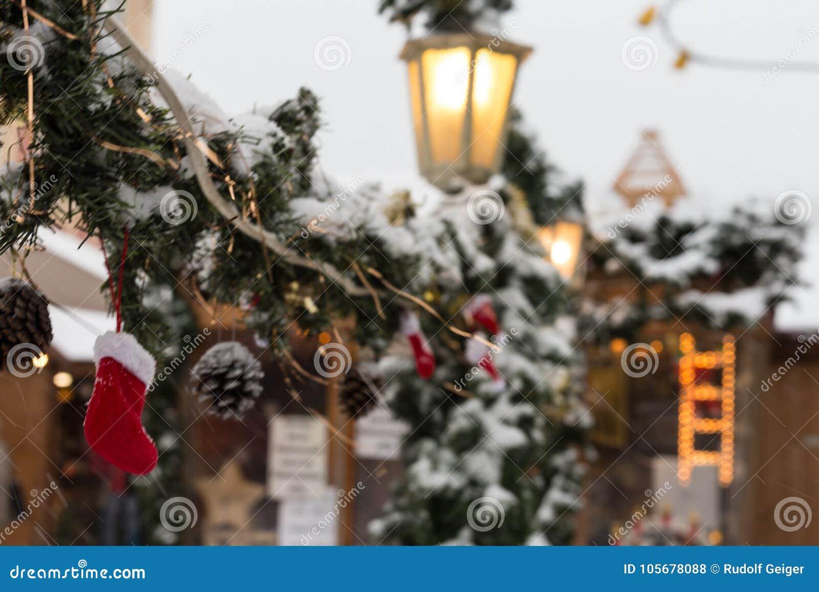 Snöfall på jul marknadsför med ljuslampor och garnering in