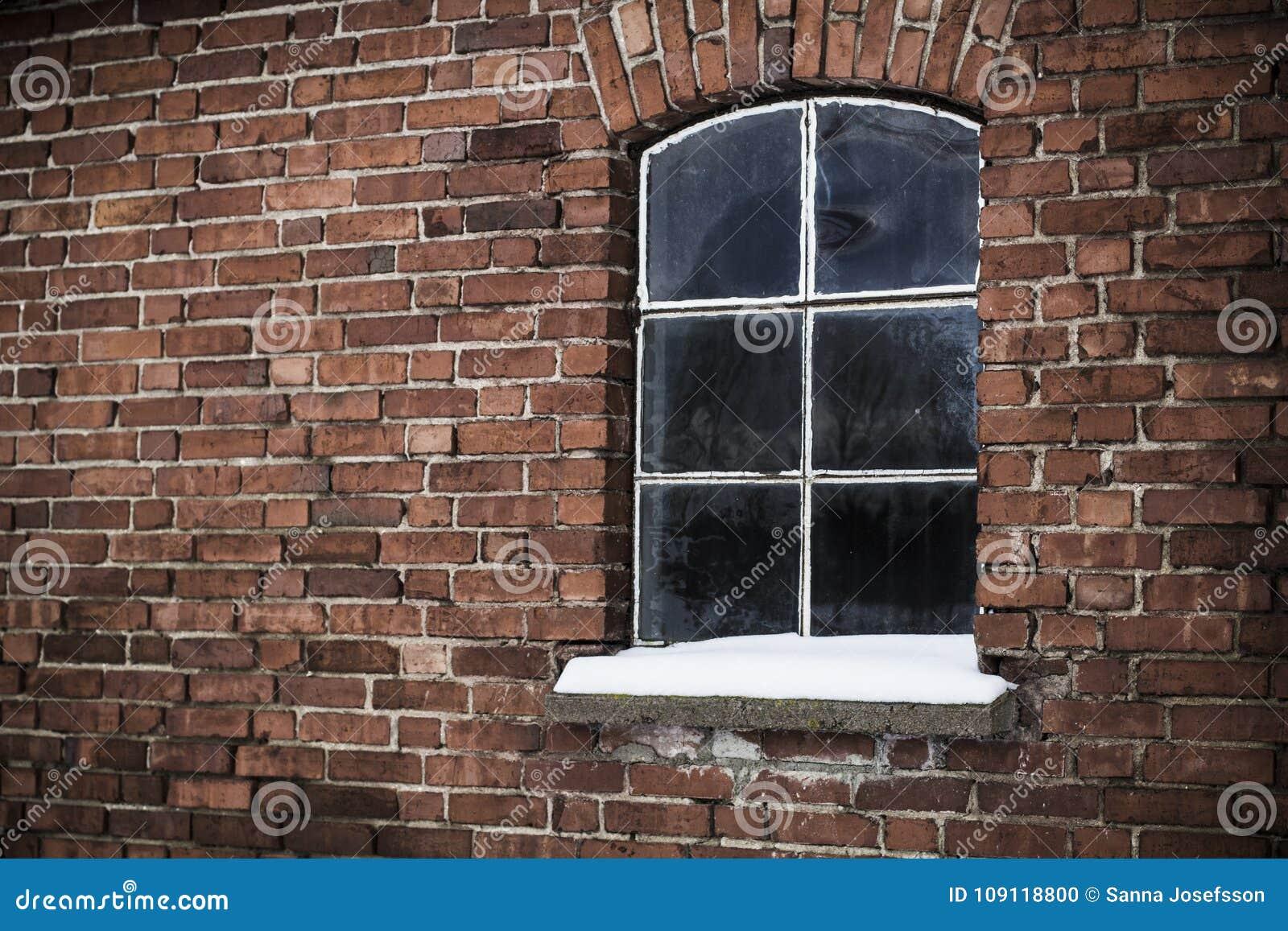 Snöig fönster för tappning, tegelstenvägg