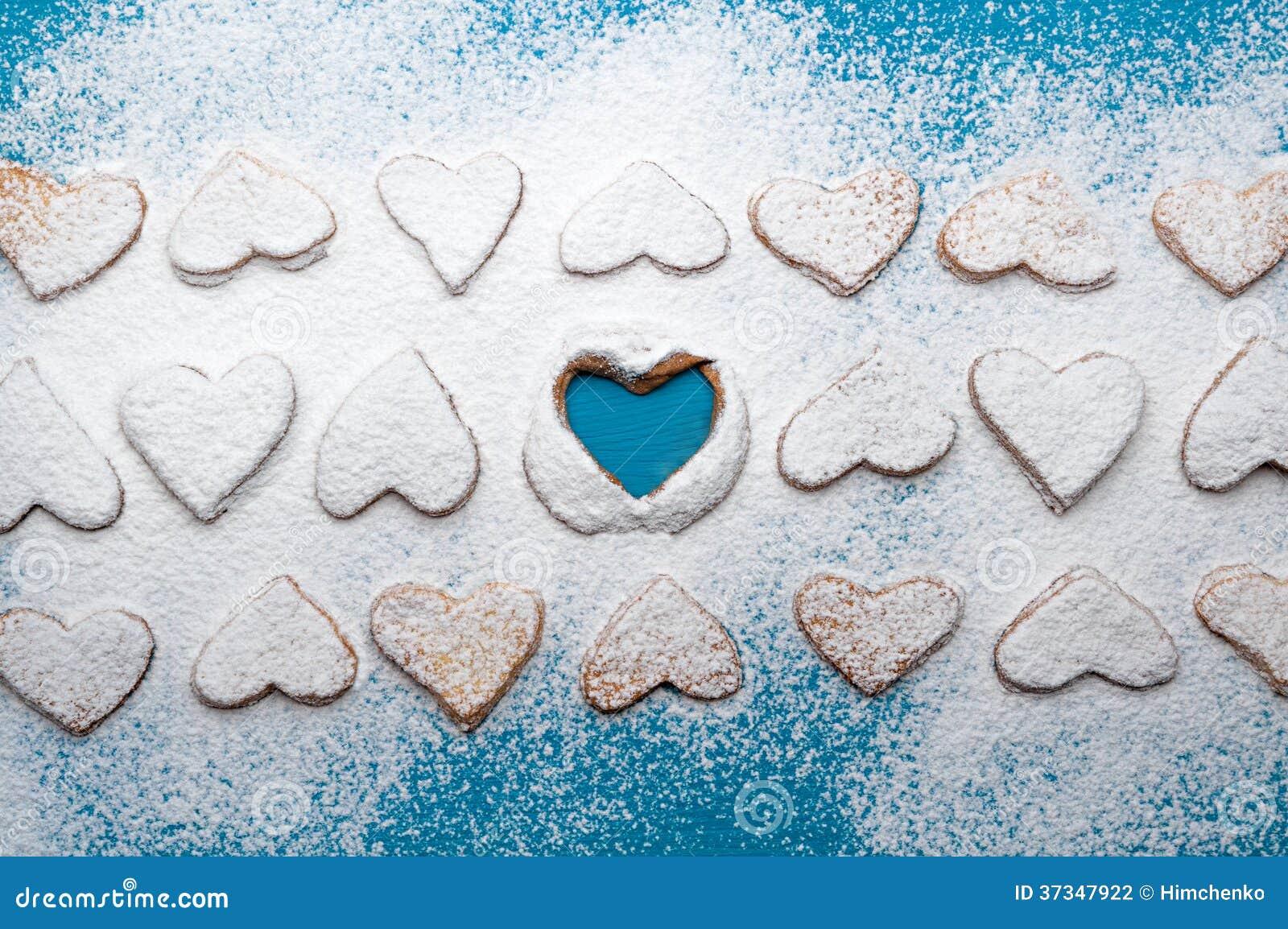 Snöig kaka-hjärtor i linjer med en tom hjärta i mitt
