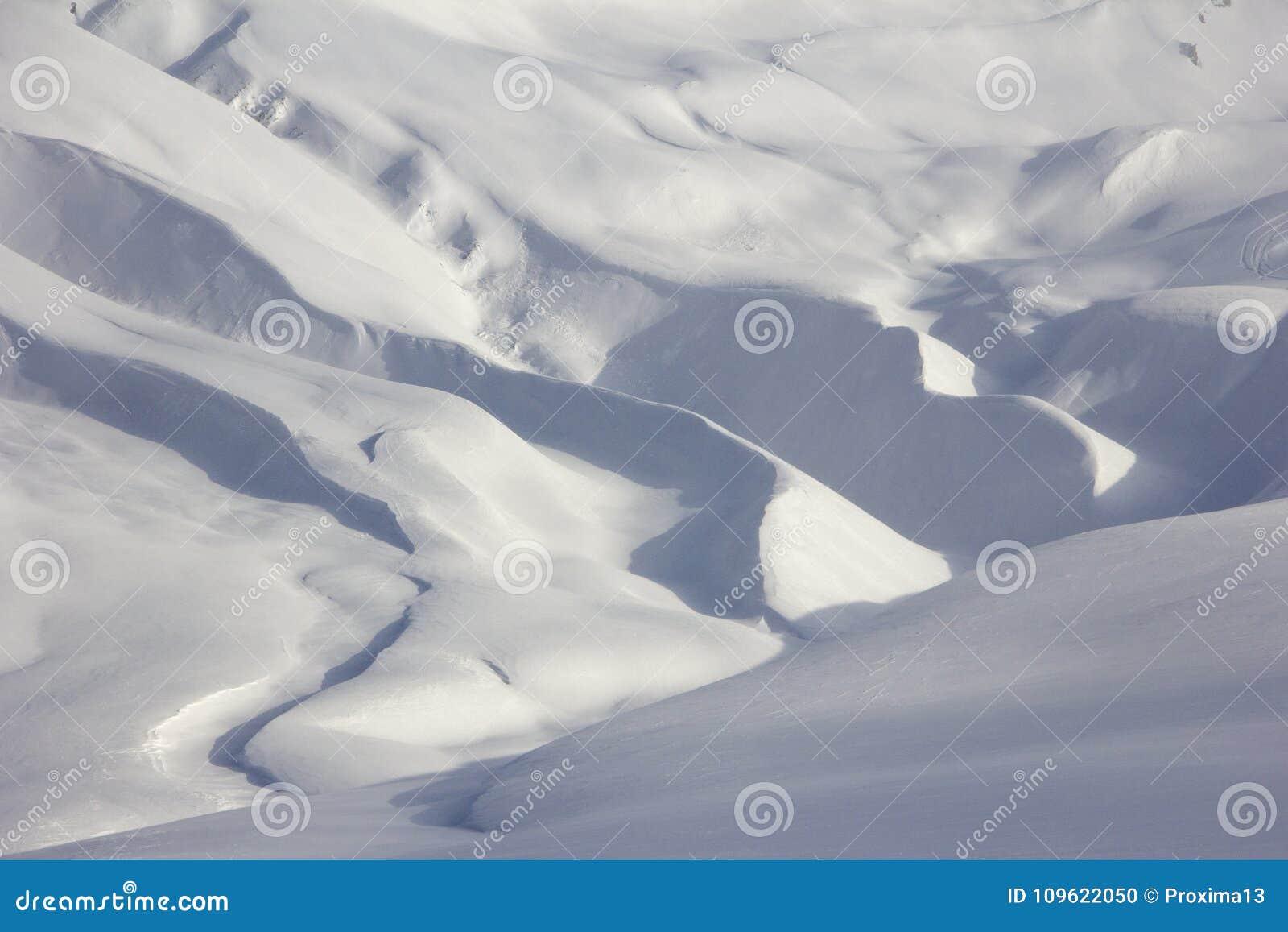 Snöig slingrande bergtopografi, skuggor av vit och blått