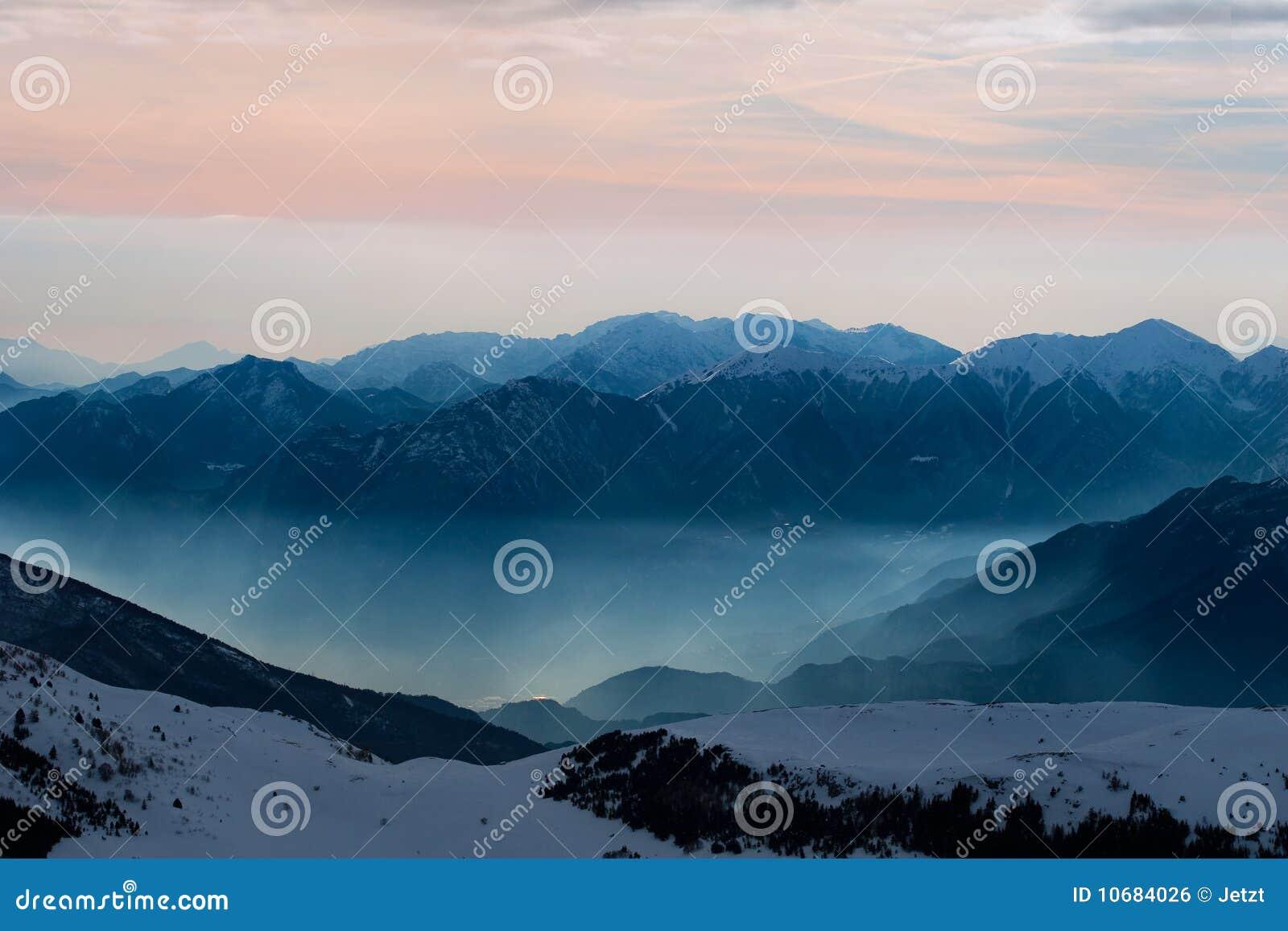 Snöig solnedgång för storartade berg