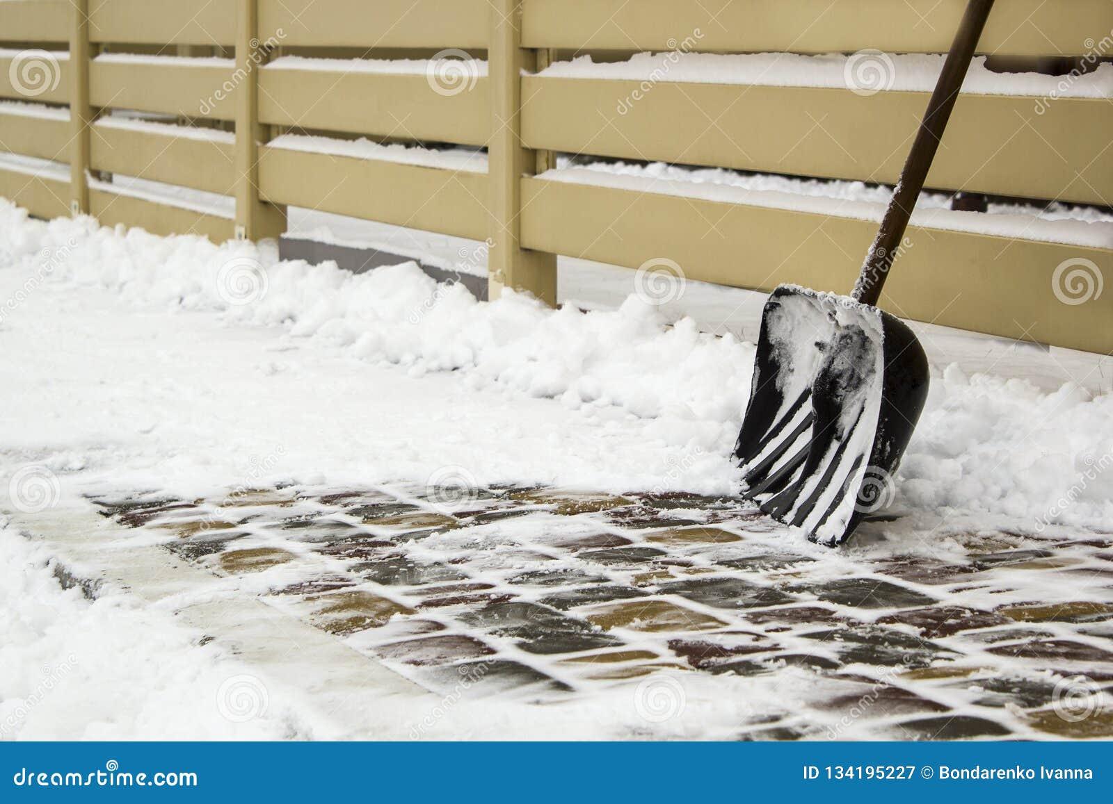 Snöskyffel nära staketet på en snöig väg