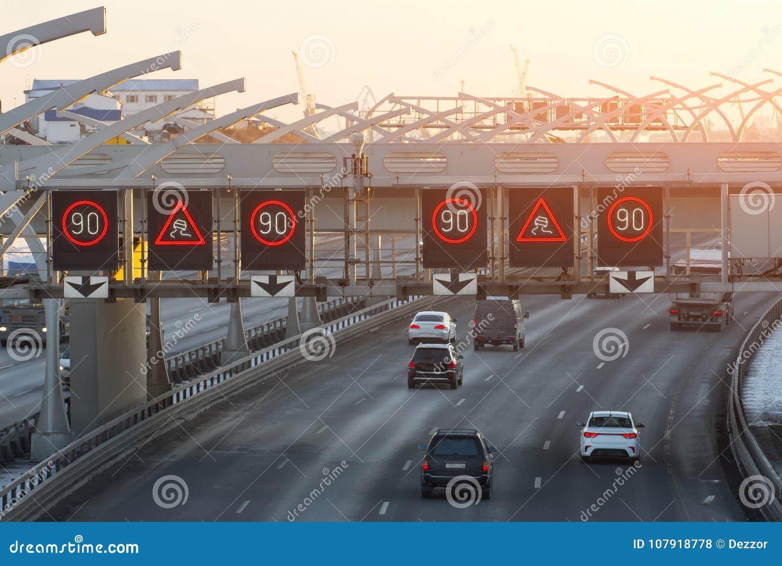 Snabb huvudväg med trafikbilar och hastighetsbegränsningtecken och en hal vägvarning