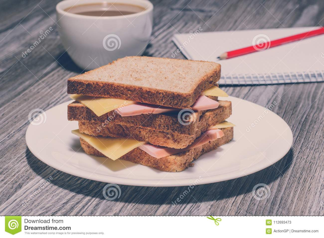 Snack education fast junk food concept. Business lunch. Tasty ham sandwich with cup of tea, notebook and a pencil. Vintage effect,