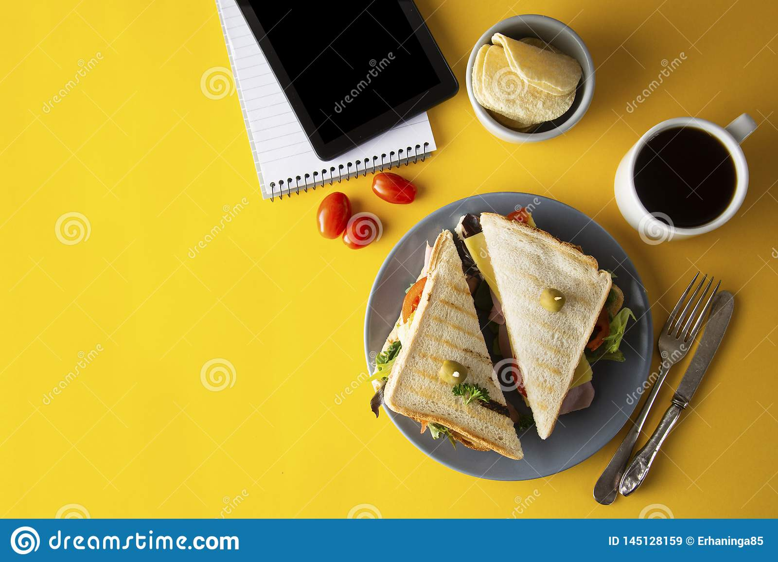 Snacks, fast food concept. Eatting at work place. Fresh club sandwich, vegetables, coffee, potato chips, sweet cookies. Tablet