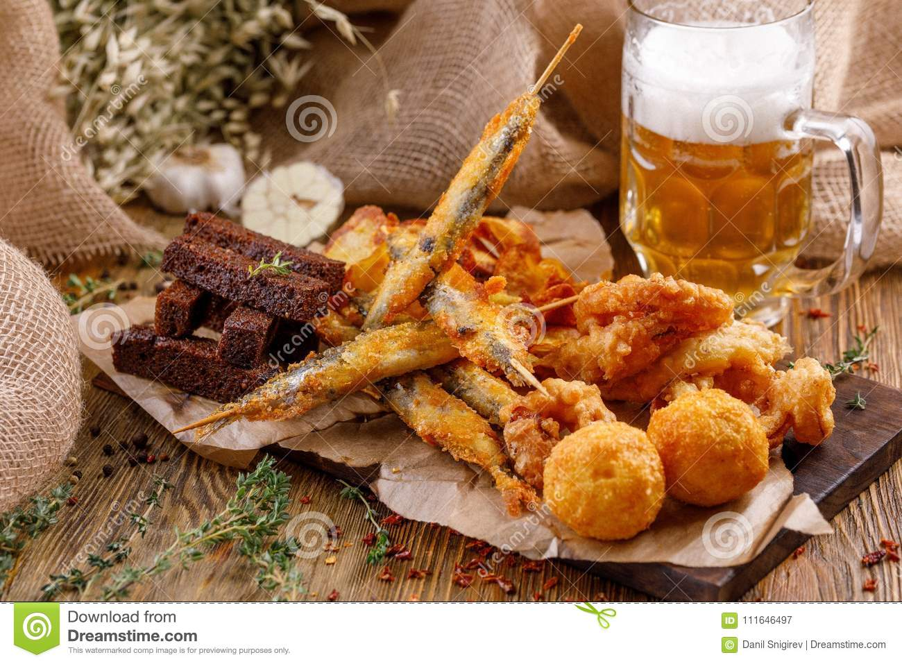 Snacks to a beer plate. Still-life on a wooden background.