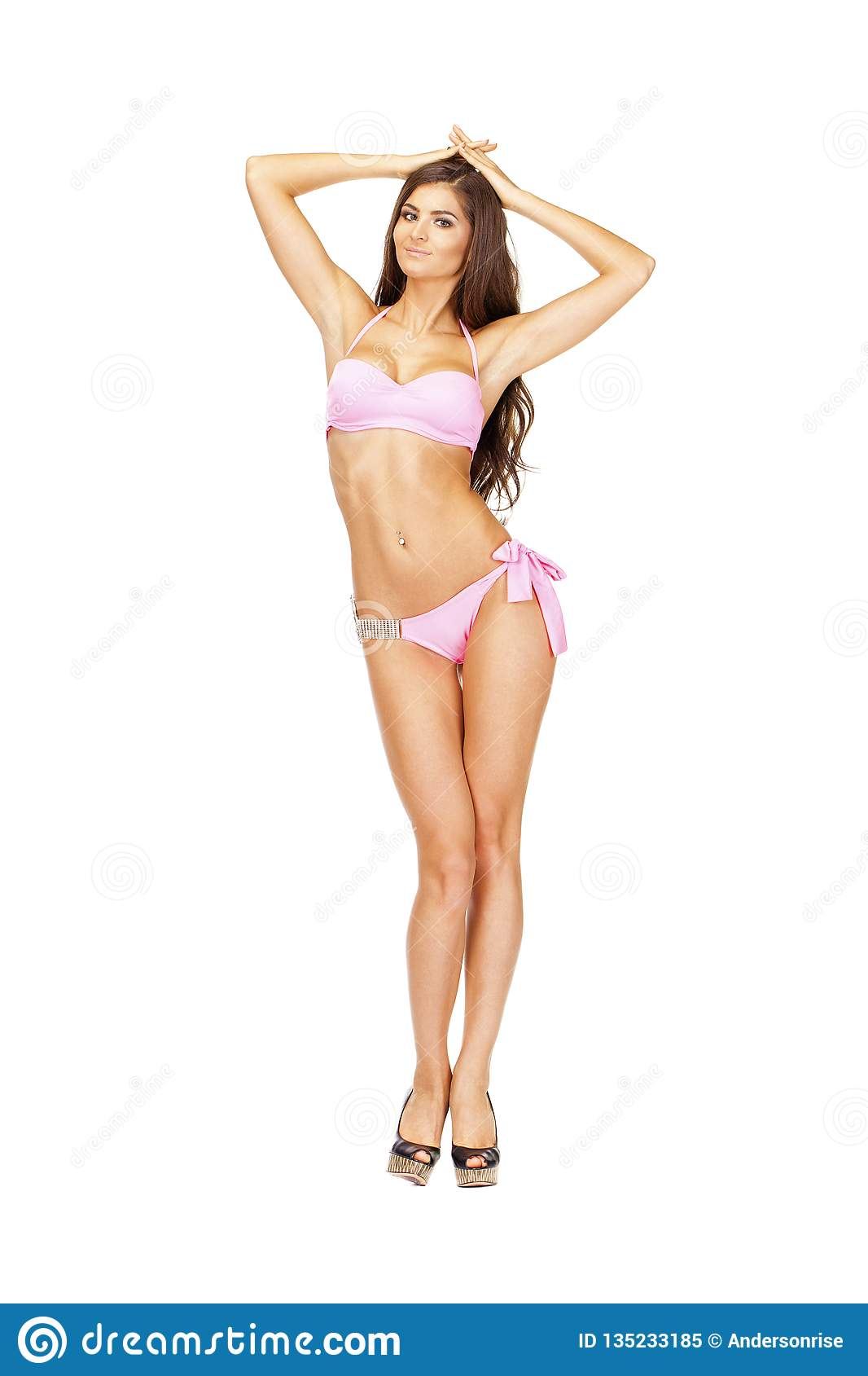 a067d8352c4 Beautiful young brunette woman in pink swimwear standing in full growth and  isolated on white background