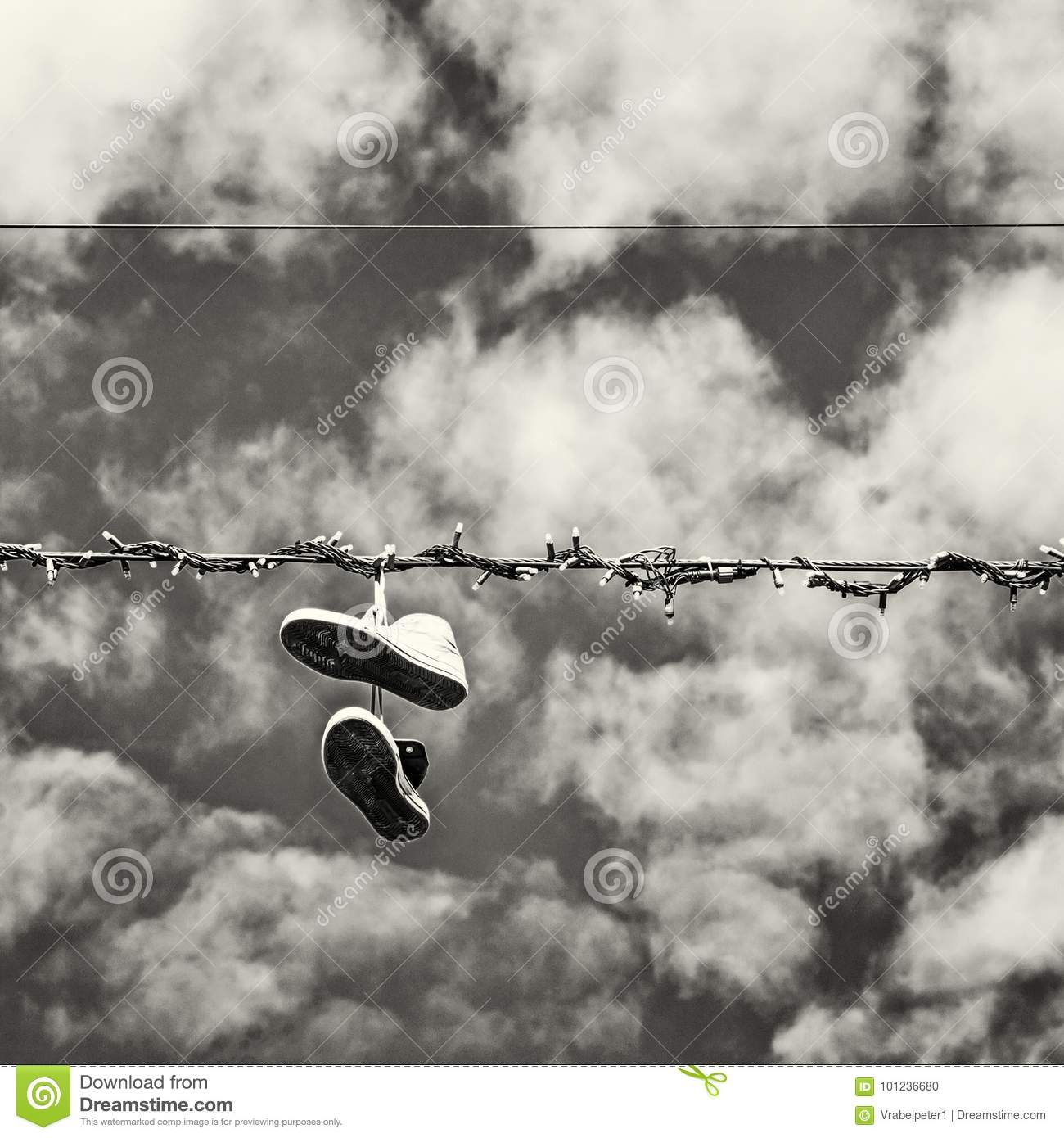 Sneakers hanging on the power line blue sky bad joke black and white photo