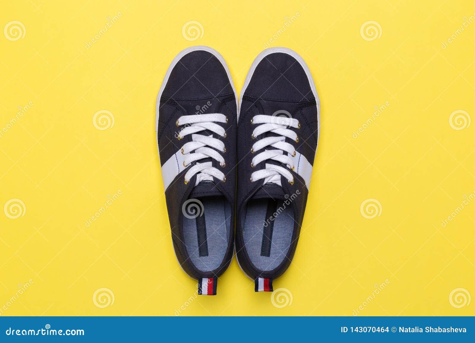 Sneakers na żółtym tle Moda magazynu lub blogu pojęcie