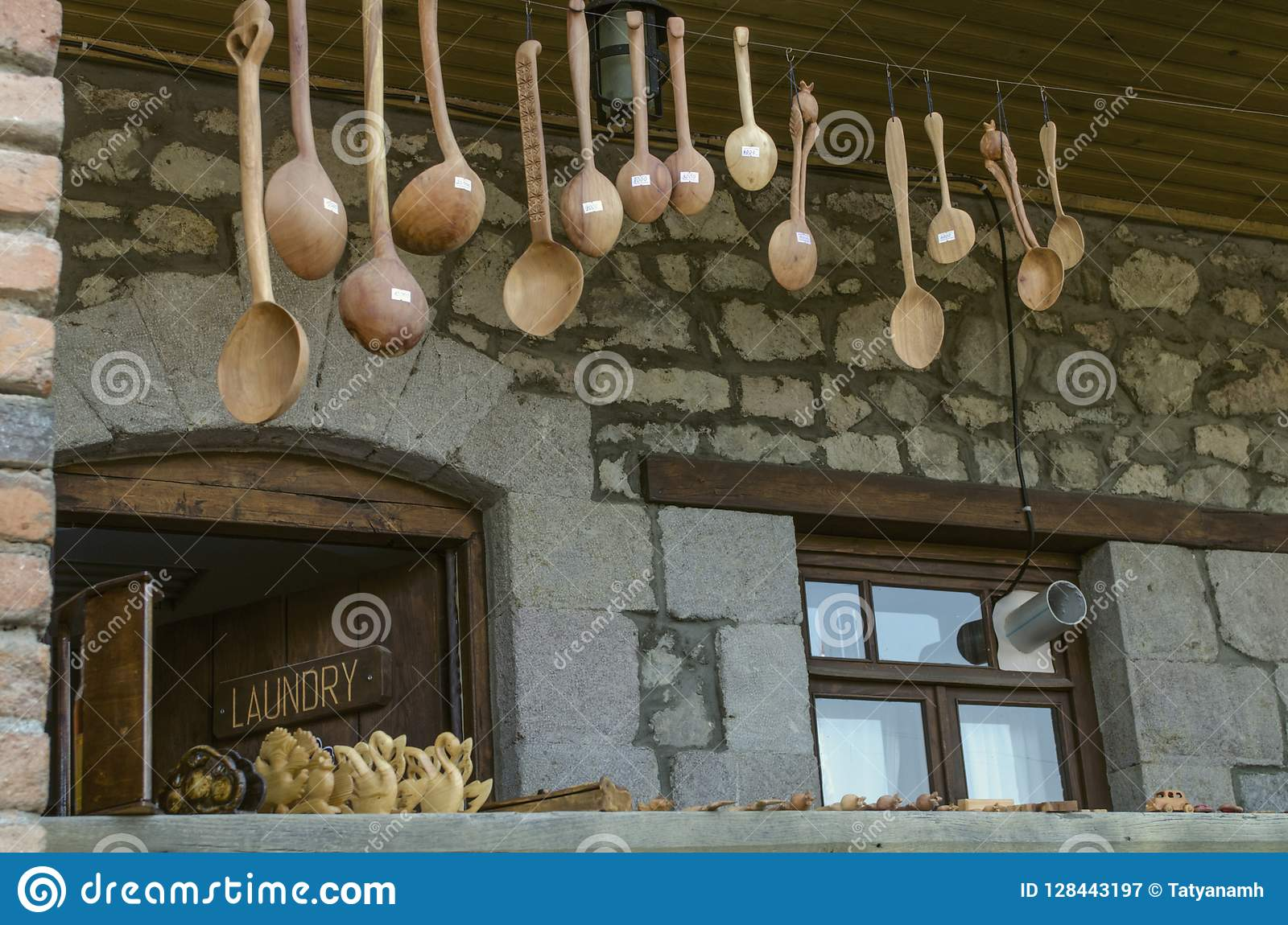 Sned träsouvenir, skedar och leksaker på verandan med tegelstenkolonner på den Sharambeyan gatan i det Tufenkian museet gamla Dil