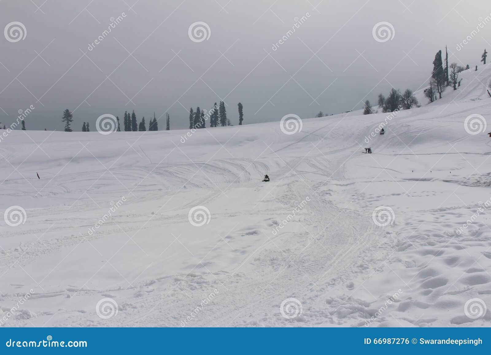 Sneeuw mobiles in afstand op sneeuw behandeld gebied in Gulmarg, Kashmir