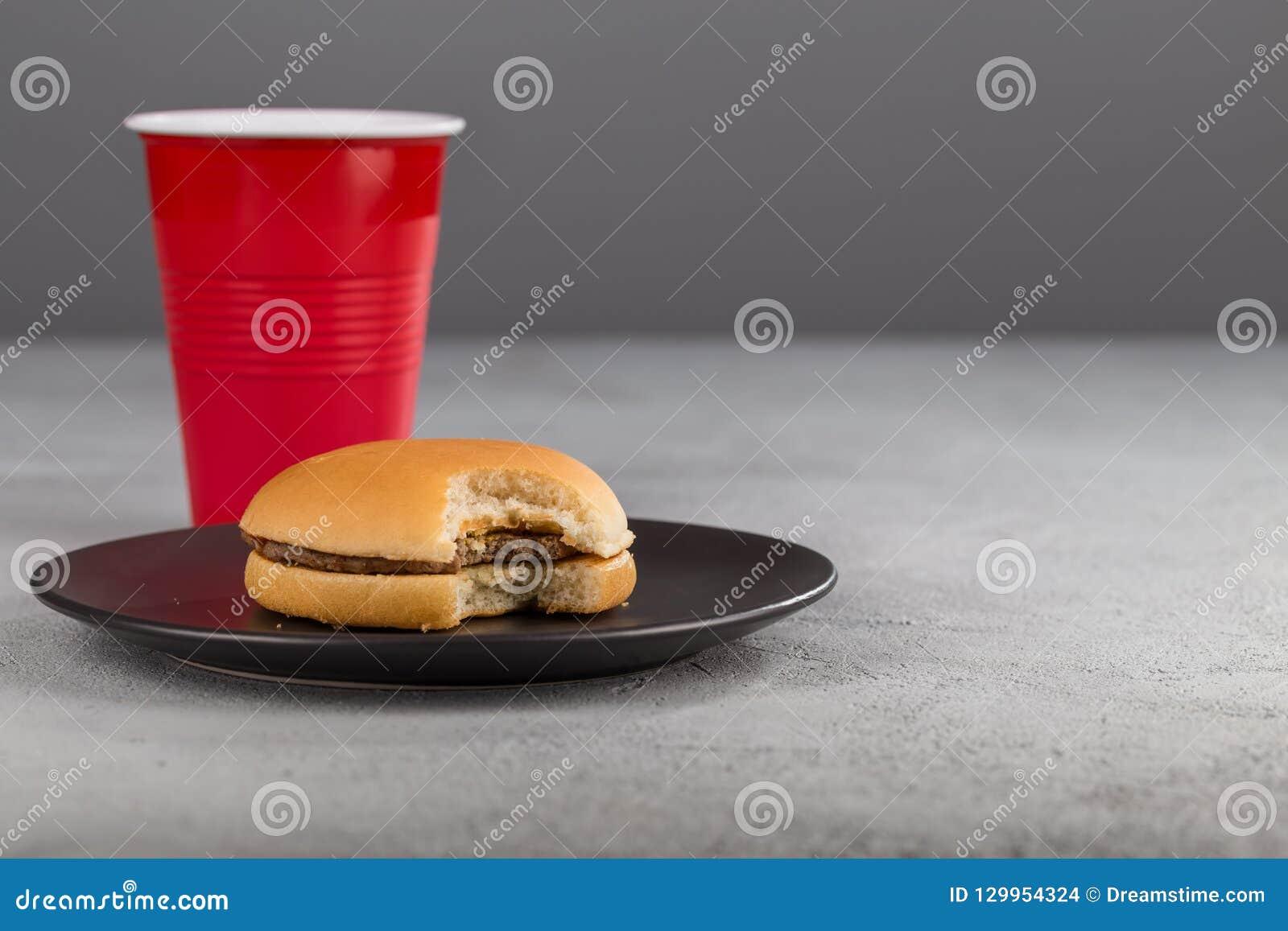 Snel voedsel met heerlijke gebeten hamburger op de achtergrond van een rode Kop met een drank