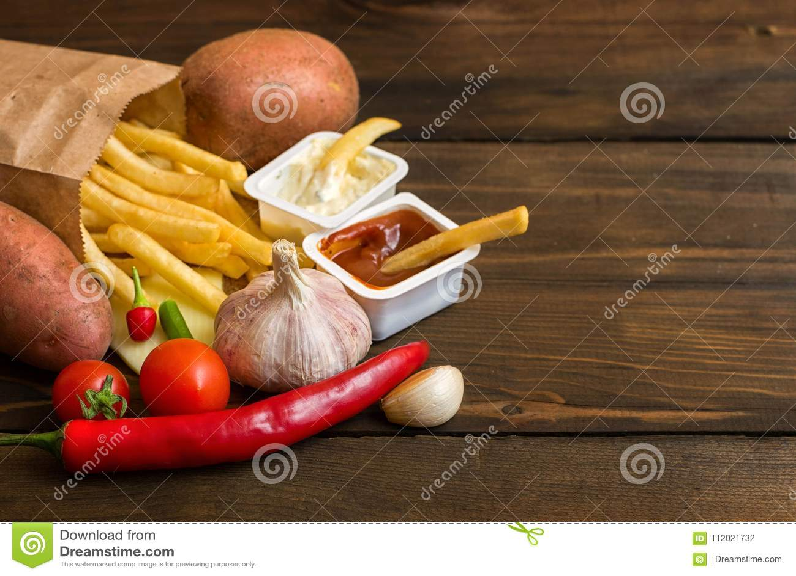 Snelle voedingsmiddelen: frieten met saus en voedselingrediënten op donkere houten lijst met exemplaar ruimte, hoogste mening