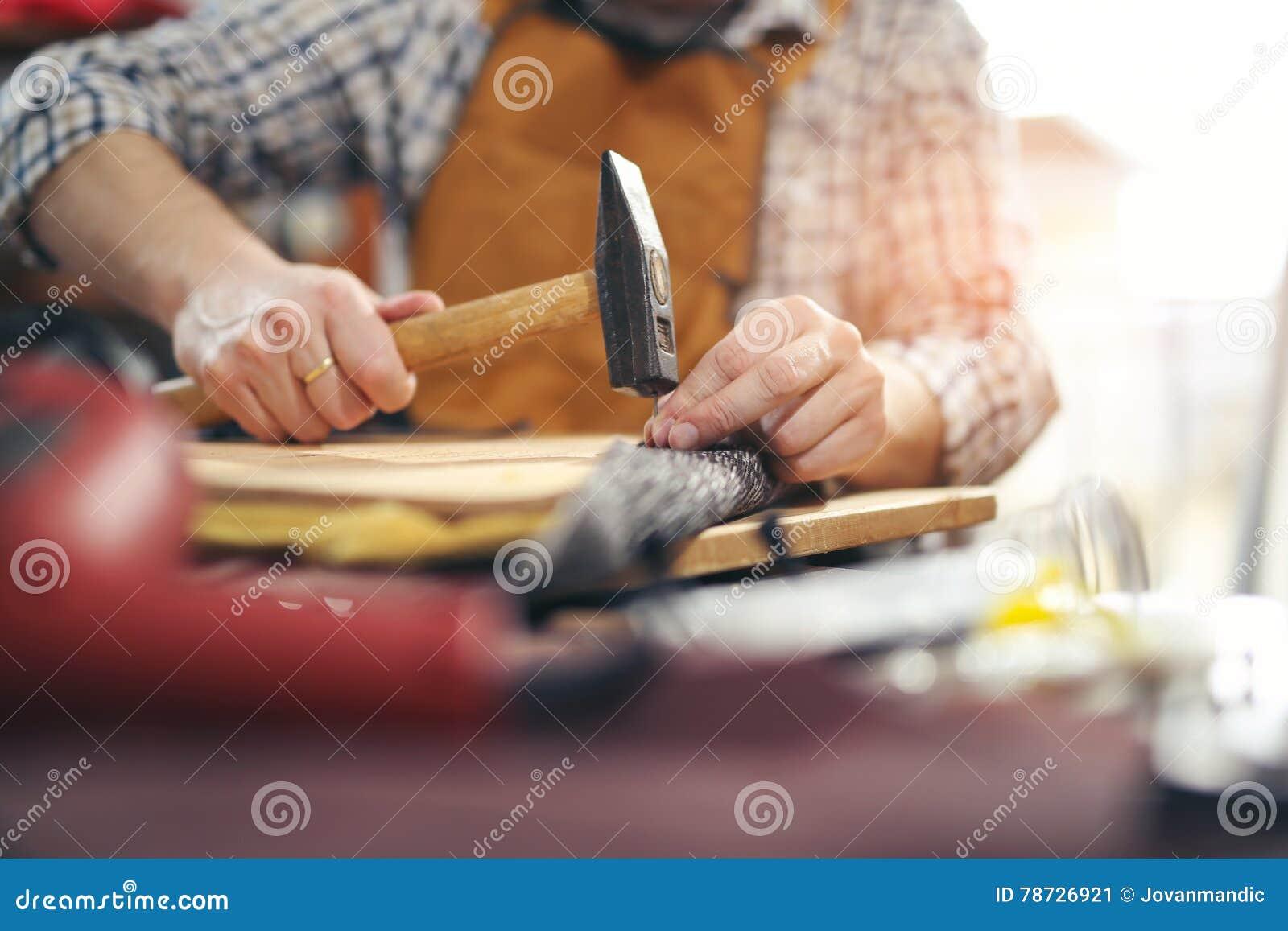 Snickare som arbetar med hammaren i hans seminarium