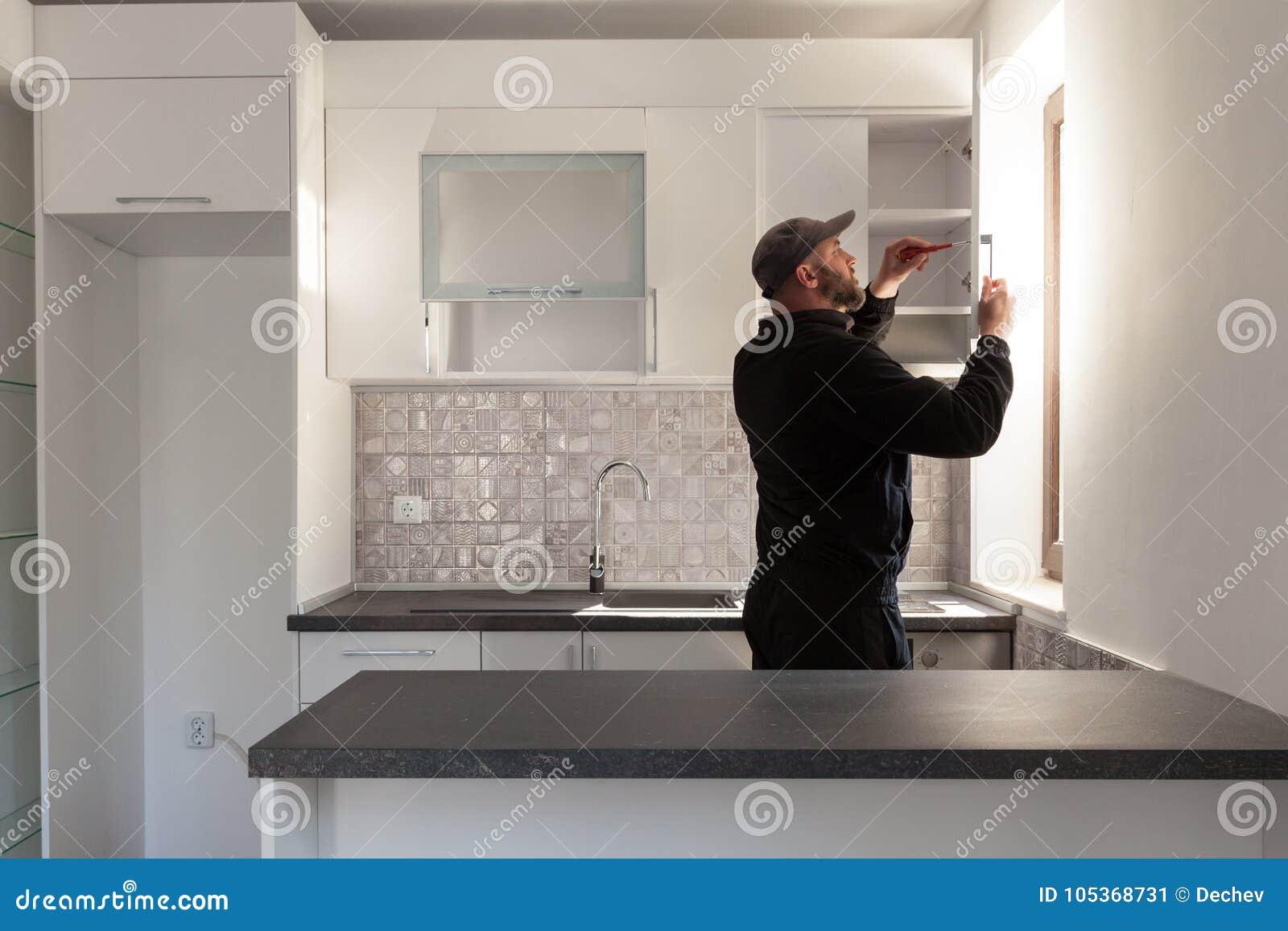 Snickare som arbetar på nytt kök Faktotum som fixar en dörr i ett kök