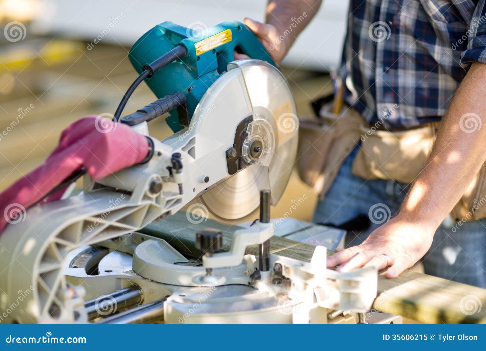 Snickaren Cutting Wooden Plank med tabellen såg på