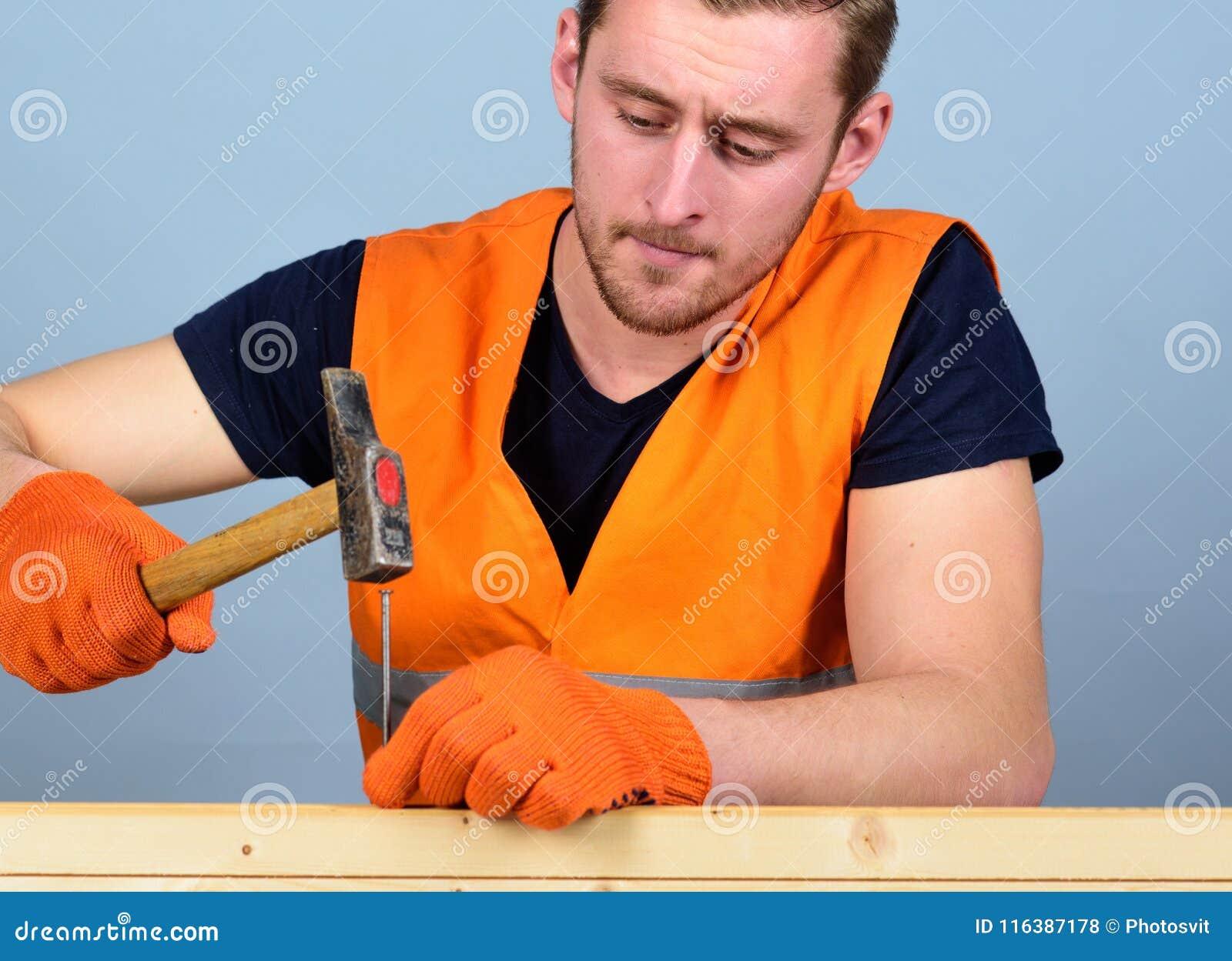 Snickaren inredningssnickare på koncentrerat bulta för framsida spikar in i träbräde Man, faktotum i ljus väst och skyddande
