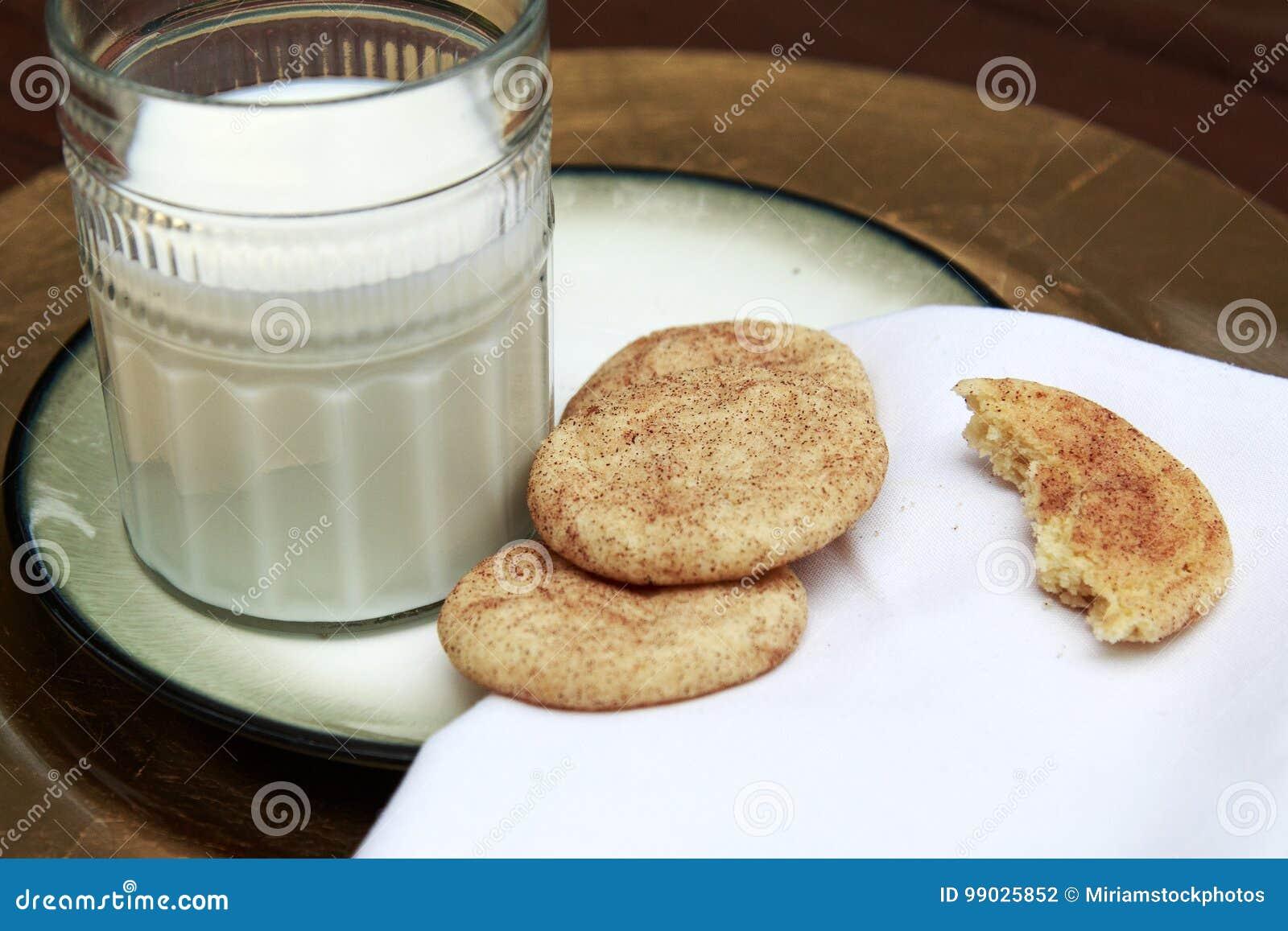 Snickerdoodle kakor på den guld- plattan med exponeringsglas av mjölkar