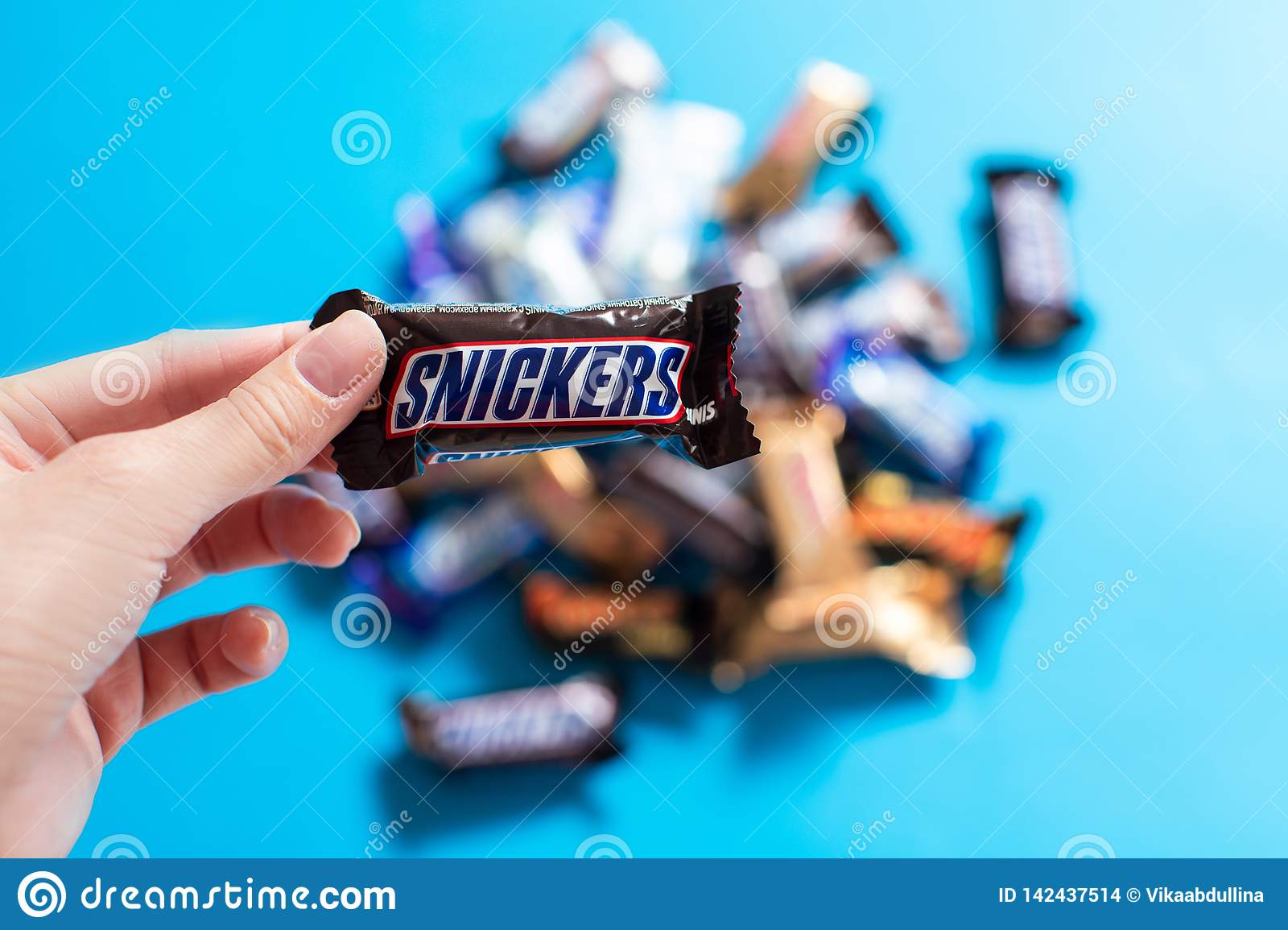 Snickers in hand - popular mini candy chocolate bars on blue background