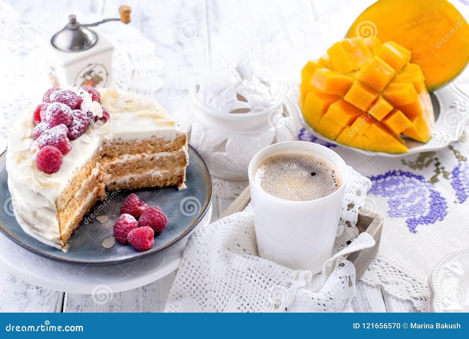 Snijd de cake met witte room, voor het fruit van de ontbijta mango Witte achtergrond, tafelkleed met kant, een kop van geurige zw