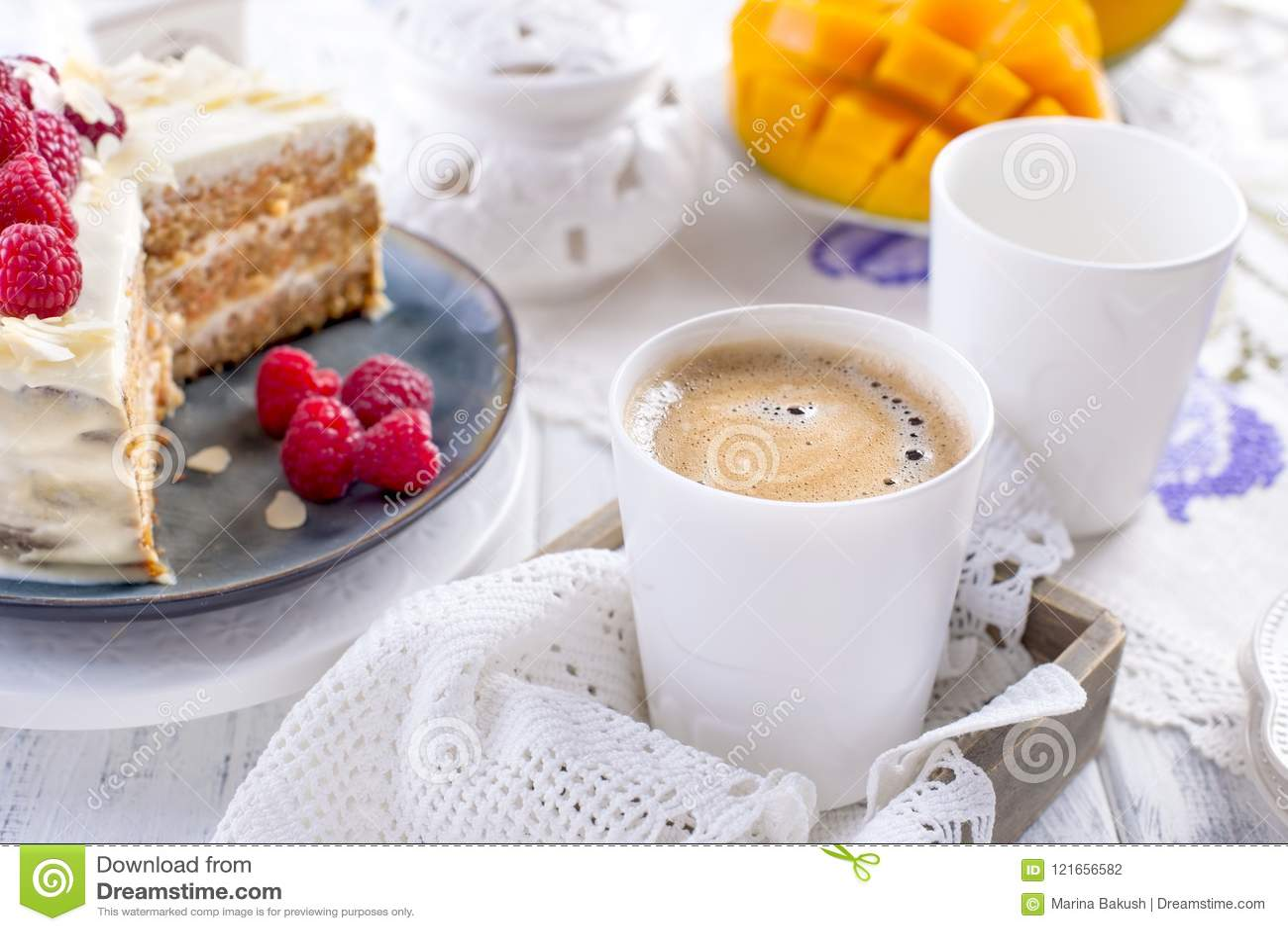 Snijd de cake met witte room, voor het fruit van de ontbijta mango Witte achtergrond, tafelkleed met kant, een kop van koffie en