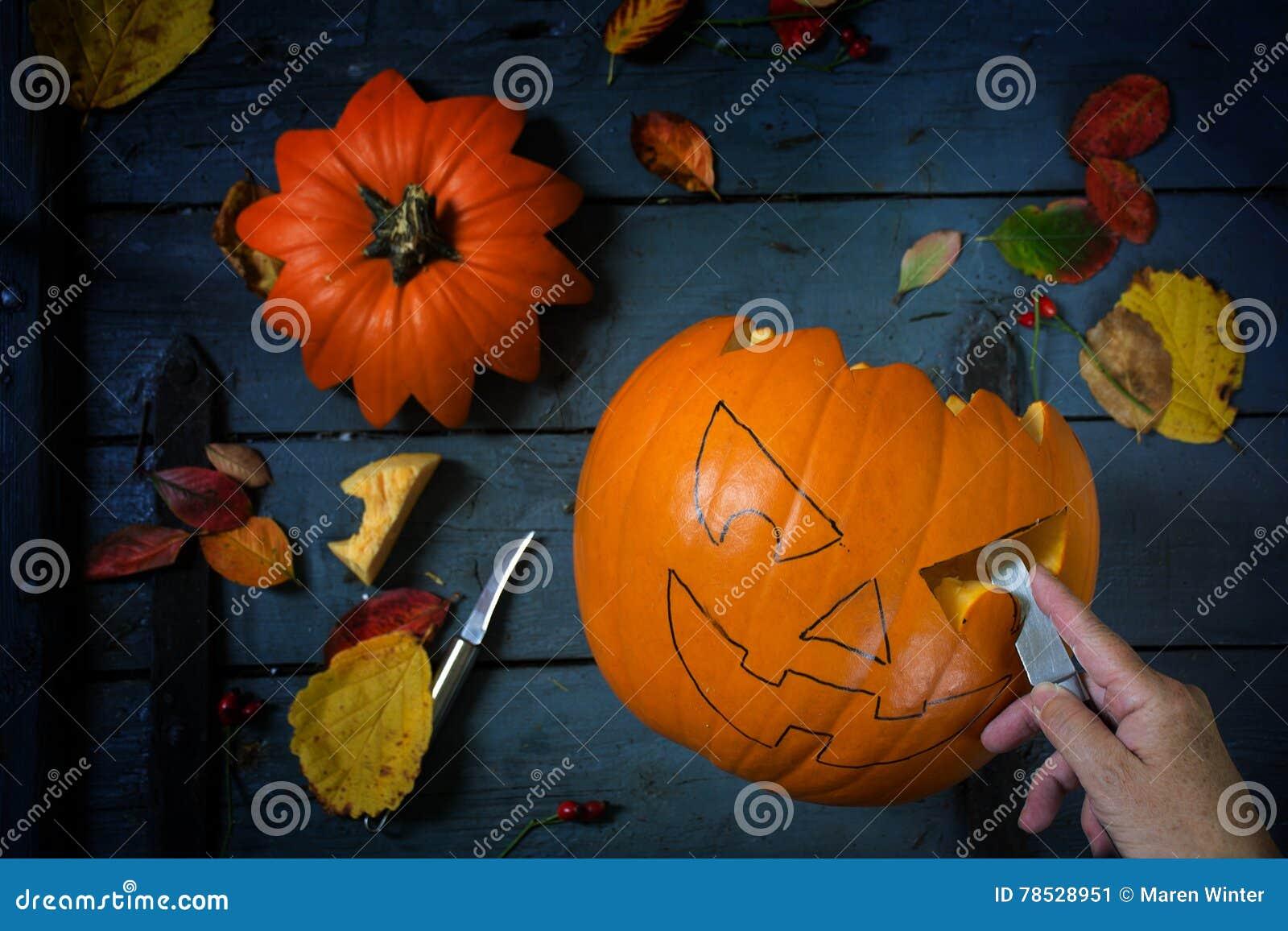 Snijd een pompoen voor Halloween of de herfstdecoratie op blauwe rusti