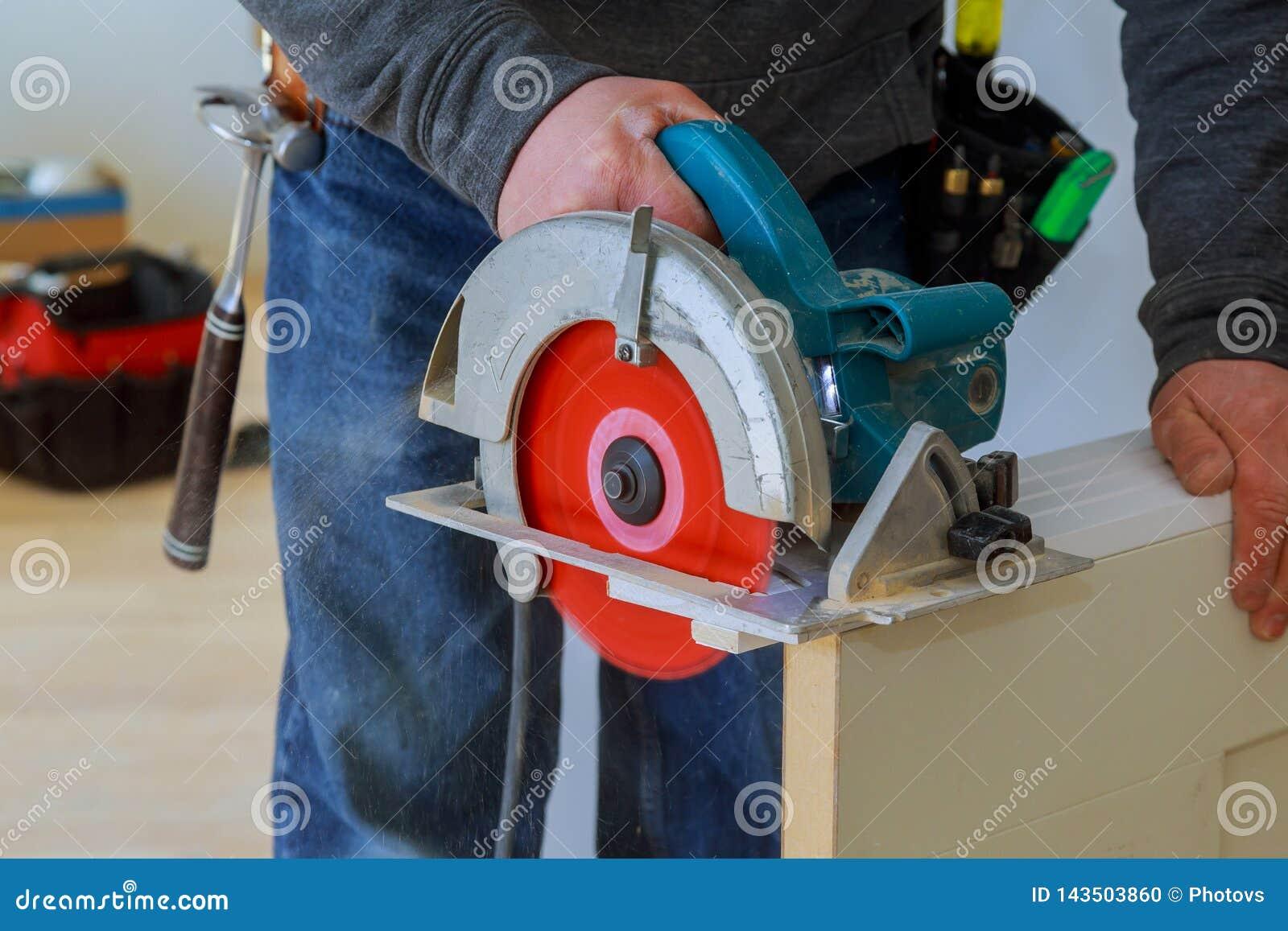 Snijdt de mensen scherpe houten deur cirkelzaag de handen van de bouwersbouw en de huisvernieuwing
