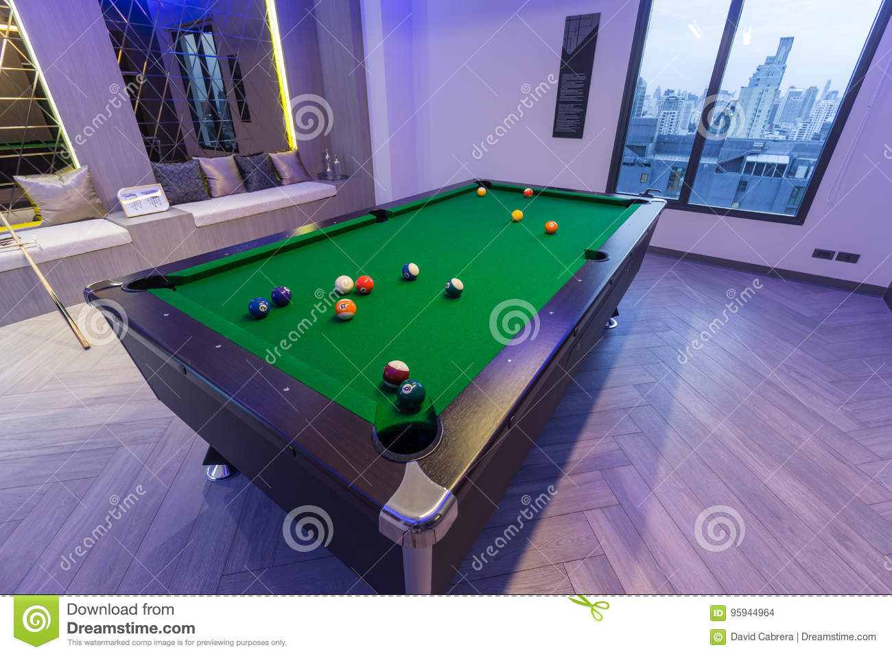 Snooker Pool Billiards green table with complete set of balls and two poo cues in a modern games room