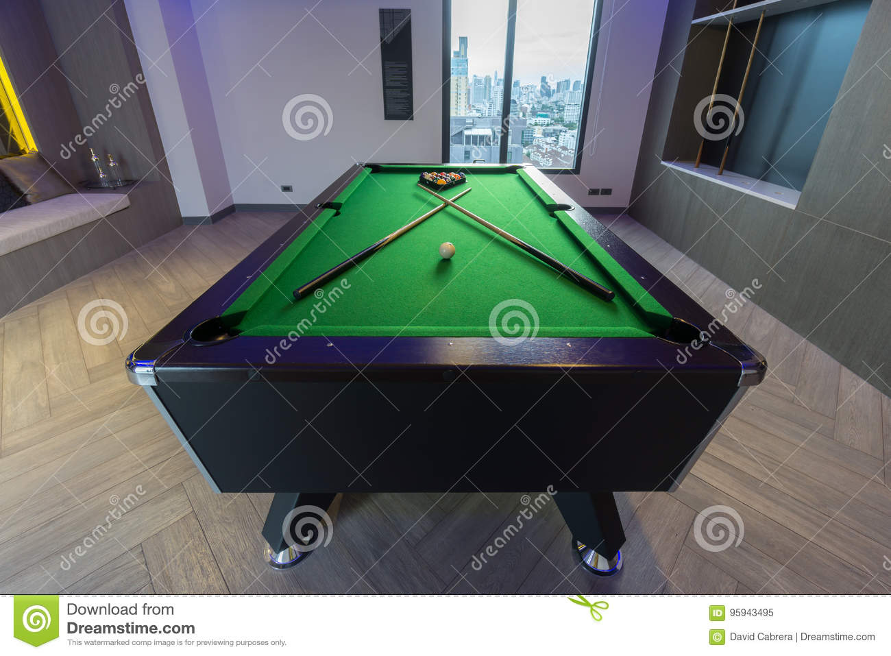 Snooker Pool Billiards green table with complete set of balls and two pool cues in a modern games room