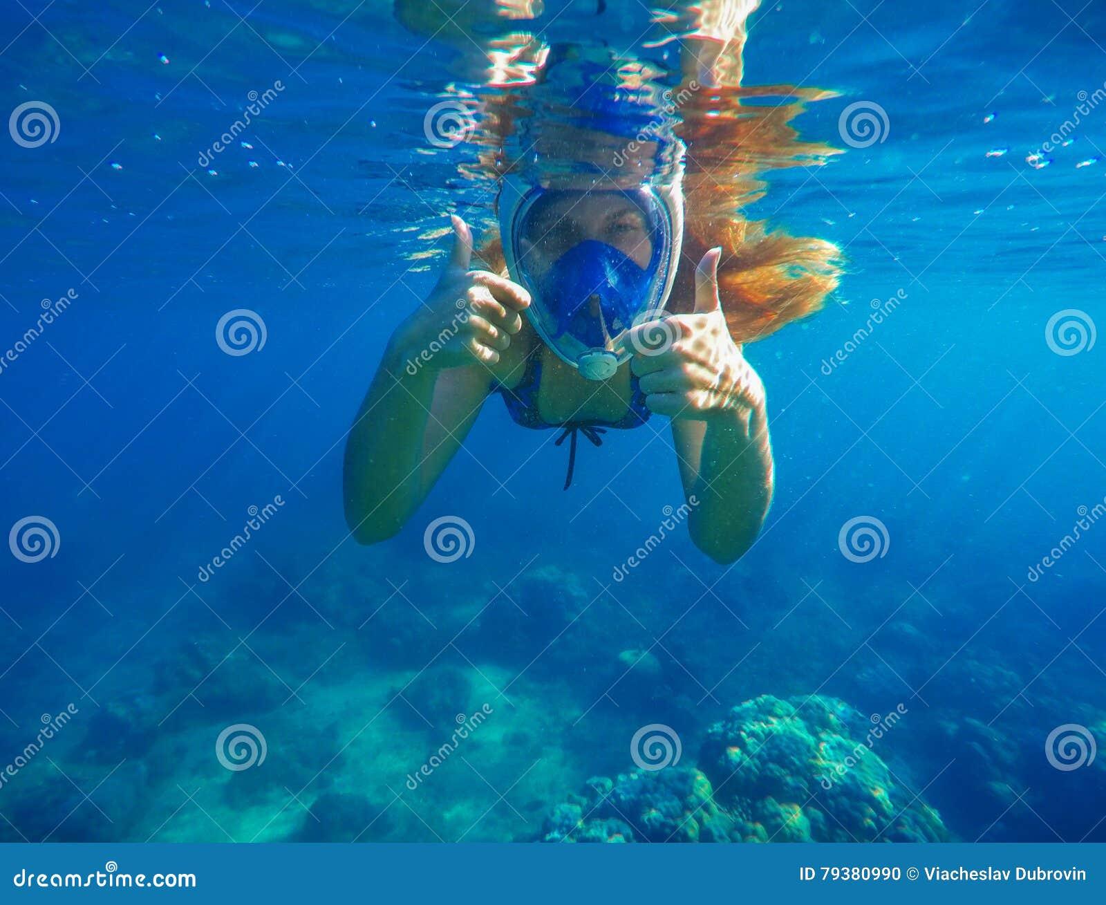 Snorkelende vrouwen onderwater tonende duimen Snorkel in volledig gezichtsmasker