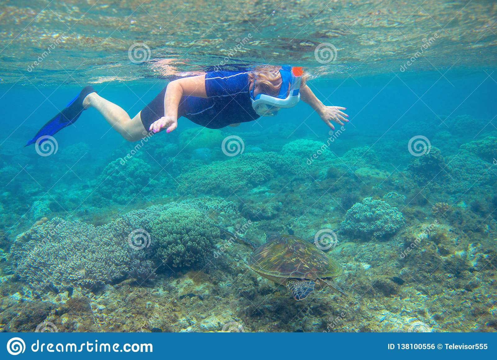 Snorkeling with sea turtle. Snorkel in coral reef of tropical sea. Woman in full-face snorkeling mask