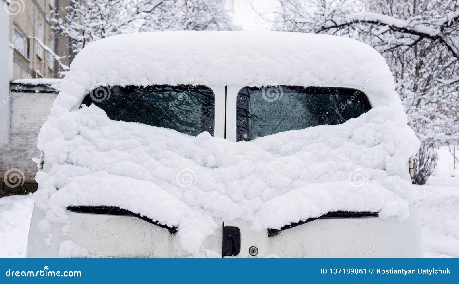 Snow on cars after snowfall. rear window, eye-like