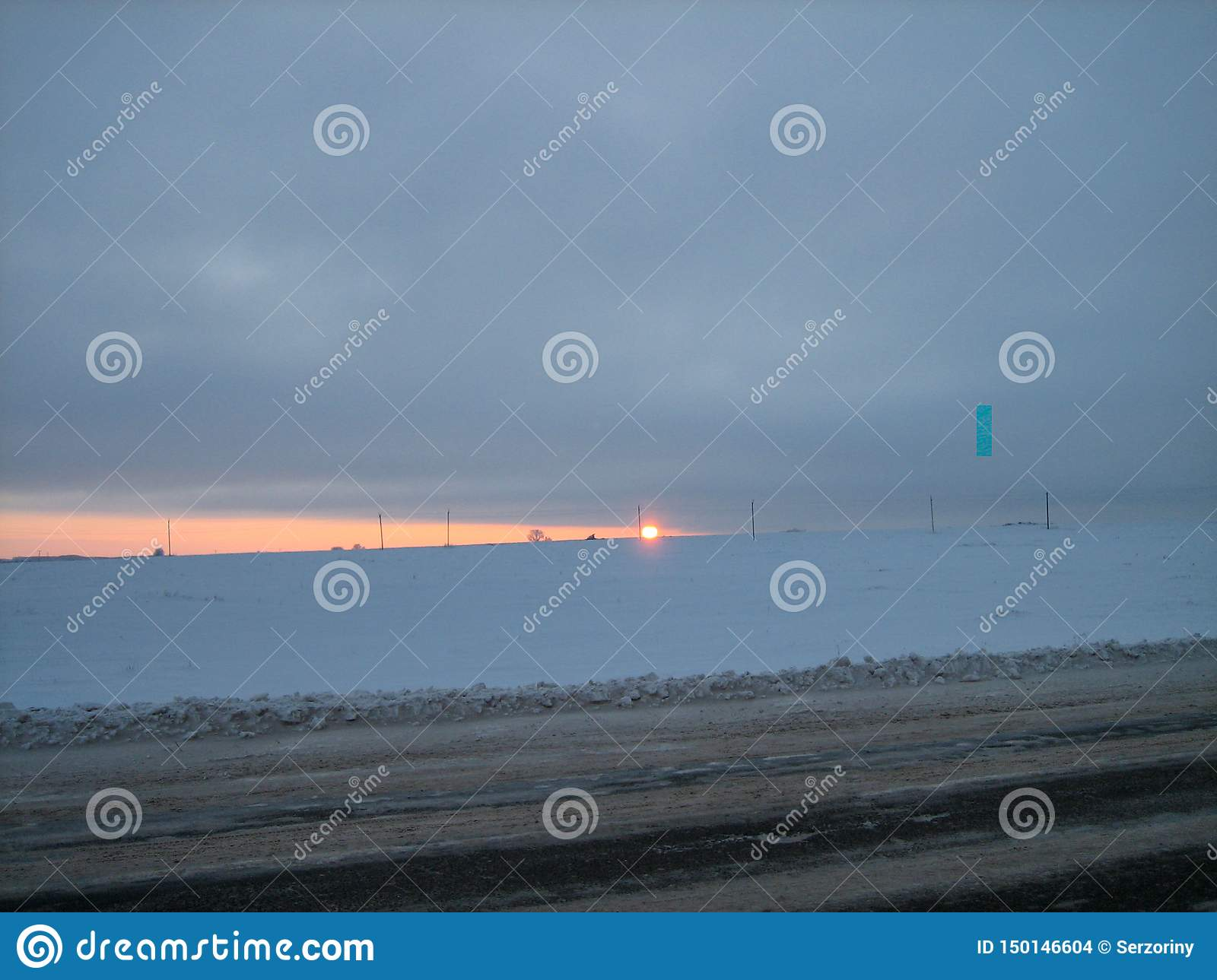 Snow-covered field along the road in the winter evening at sunset