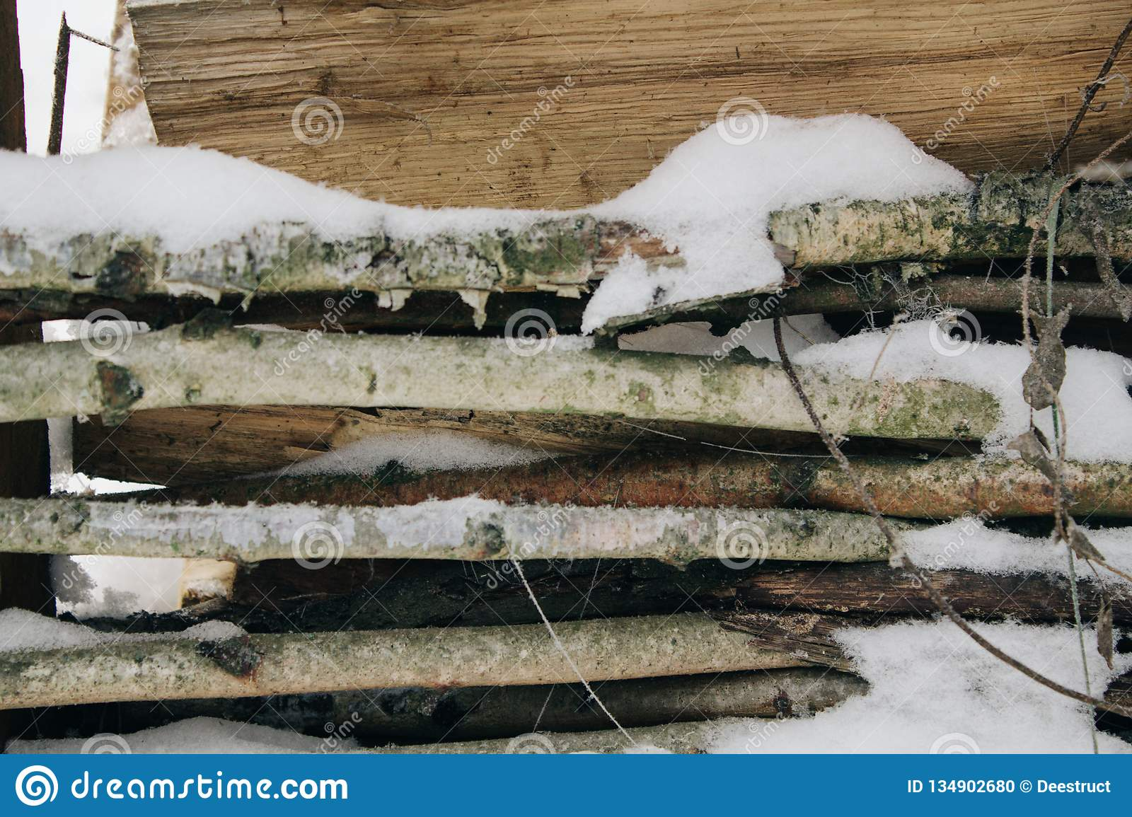 Snow-covered firewood stacked under a canopy, firewood for the winter. Winter landscape