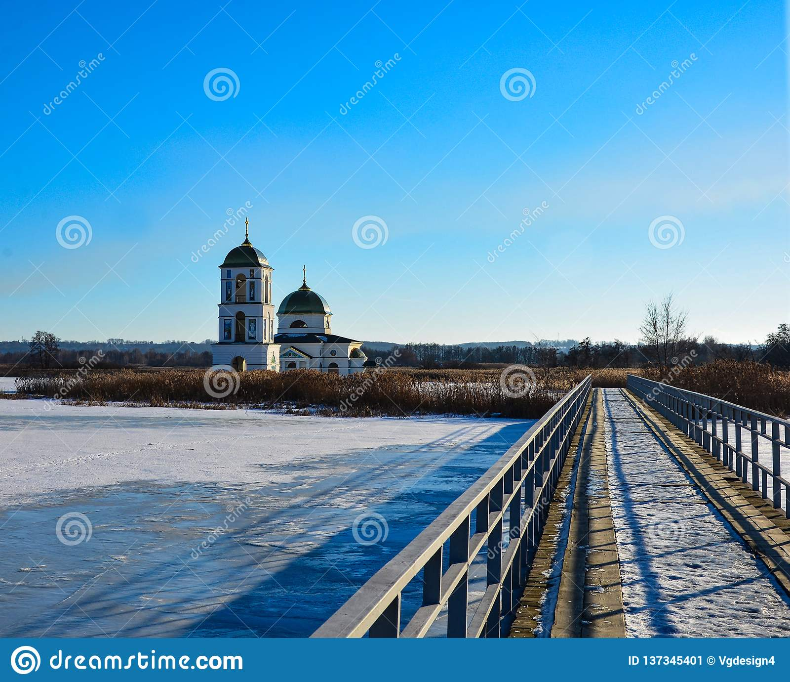 Snow-covered lake with a metal bridge towards church