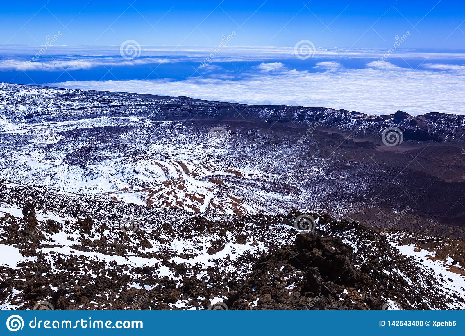 Snow-covered mountain landscape, view of the rocky landscape from the top of the mountain, volcano, clouds