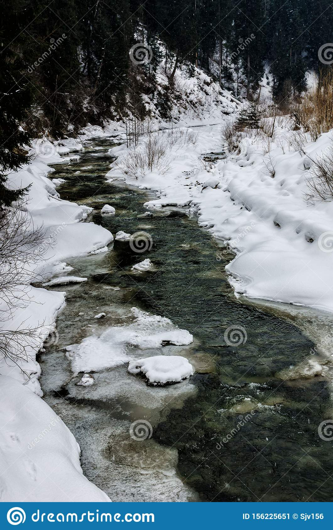 Snow-covered mountain river in the Carpathians, Ukraine, a stream of water and amazing river banks