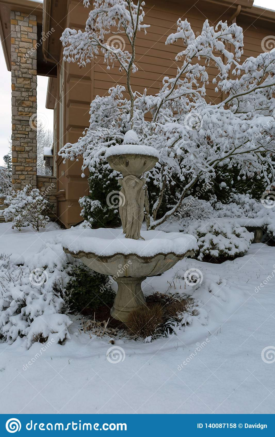 Snow Covered Water Fountain in Front Yard garden