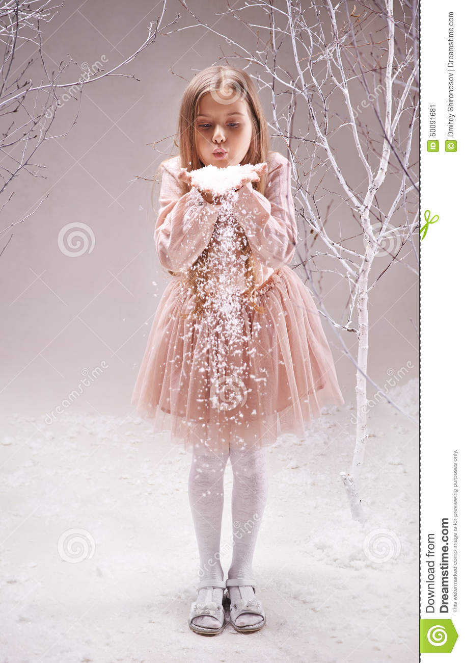 Cute little girl in smart dress blowing snowflakes from her palms in