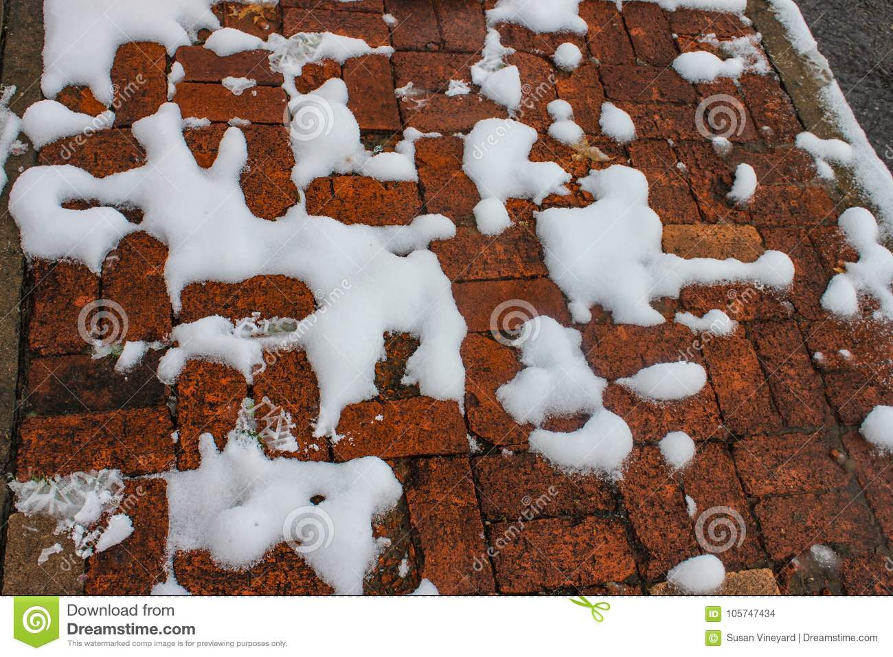 Snow melting but still visiable in blobs on orangish broken brick sidewalk