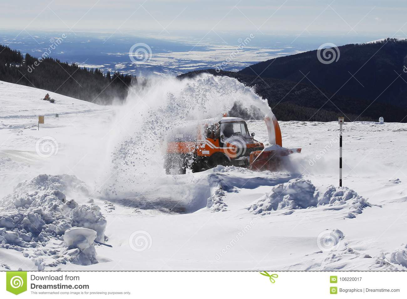 Snow removal machine blower on mountain road