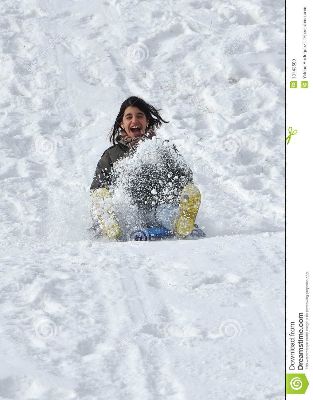 Latin Teenager Sliding Down A Snowy Steep Hill On Stock