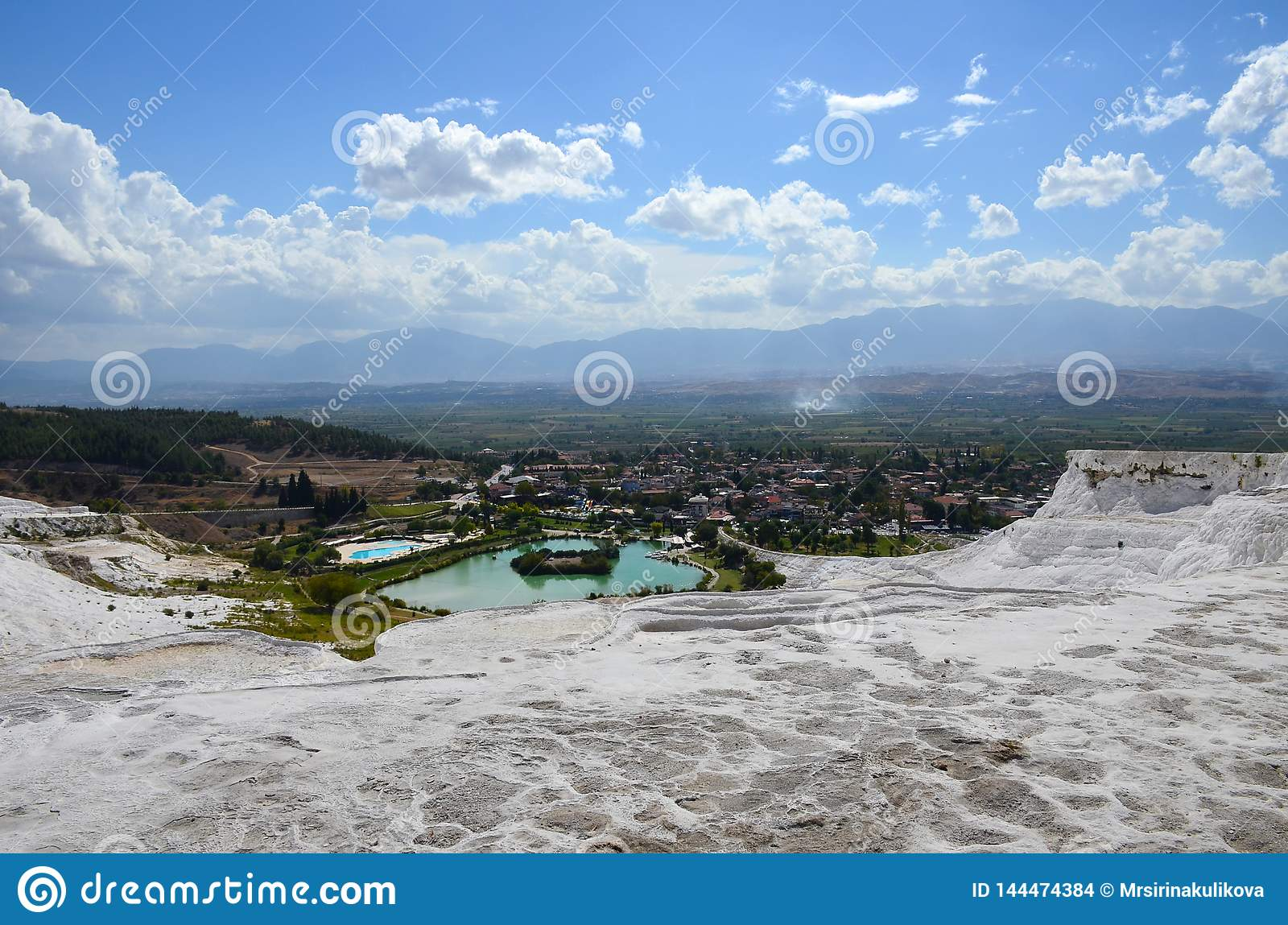 Snow-white travertines against the background of mountains, city and summer blue sky with clouds in Pamukkale, Turkey