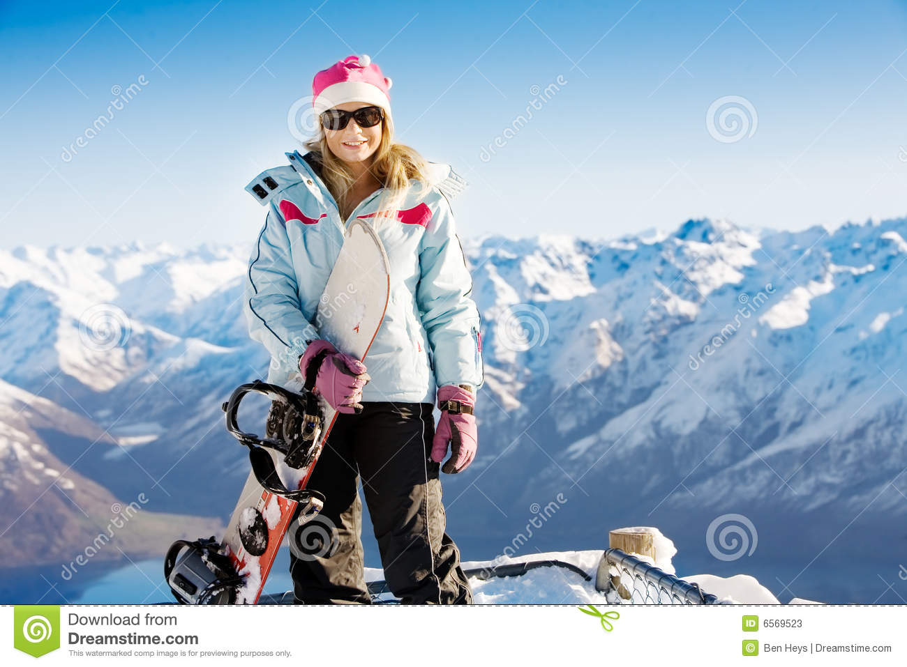 Woman holding snowboard with mountains in background.